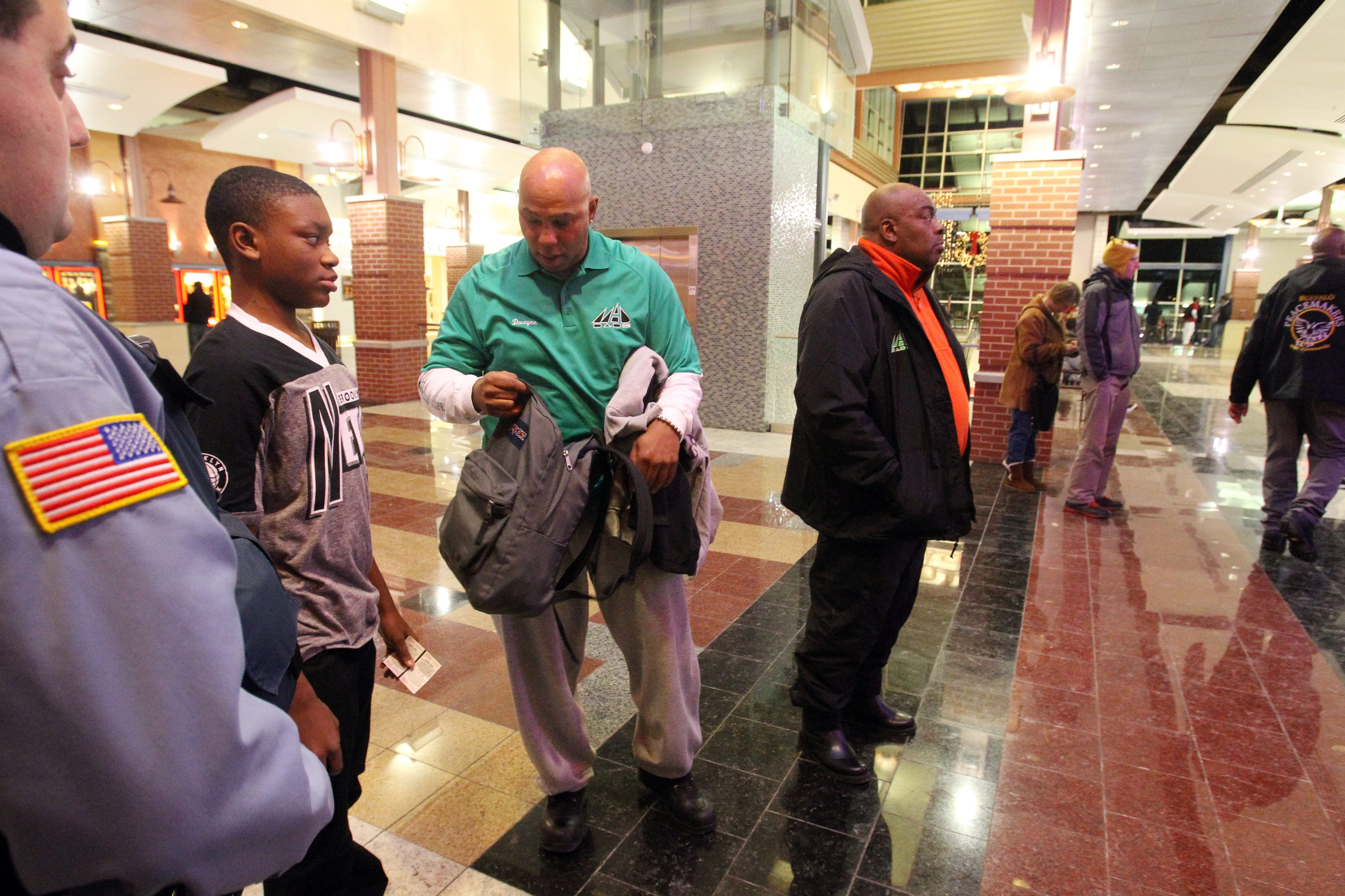 Dwayne Ferguson (green shirt) of MADDADS and the Rev. D.L. Young (in red shirt) talk to kids and inspect  their bags outside the Walden Galleria cinemas in Cheektowaga on Jan. 3, 2014.