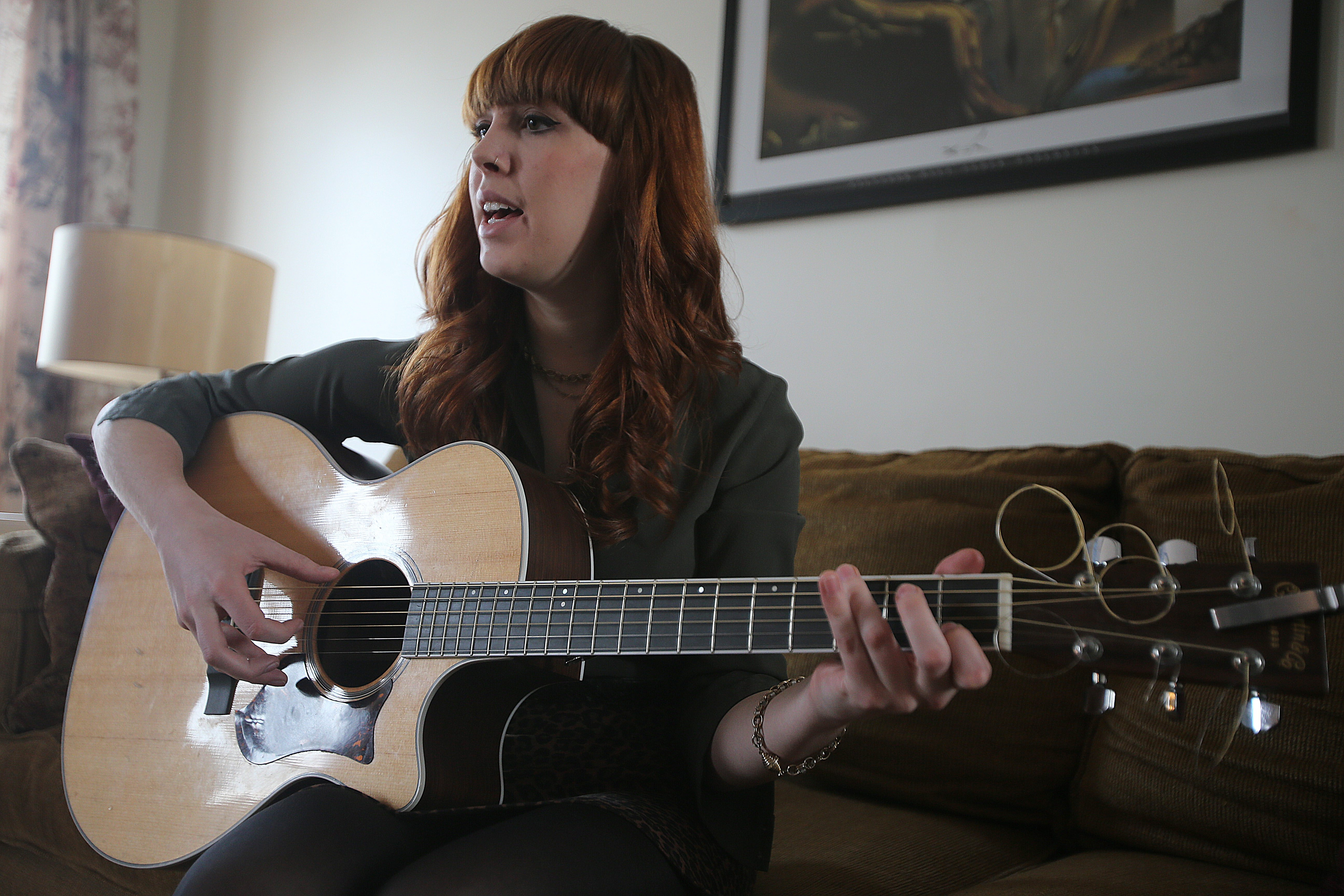 Savannah King, 20, plays guitar and sings one of her original songs at her home in Wilson earlier this month. The Fredonia State College junior is working on her third album and preparing to tour.