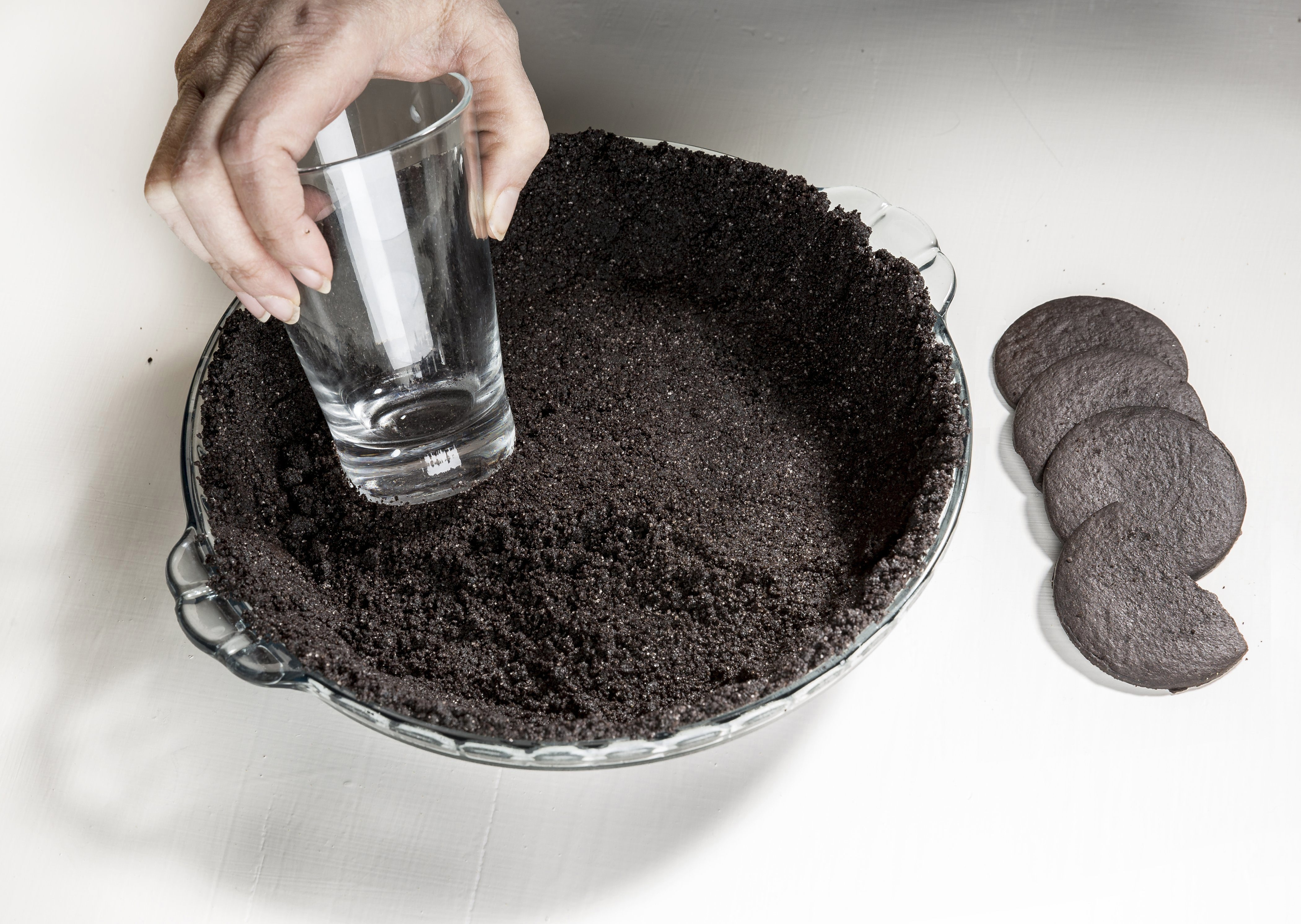 This preparation shot shows how to use a glass to press crumbs into a piecrust. (Bill Hogan/Chicago Tribune/MCT)