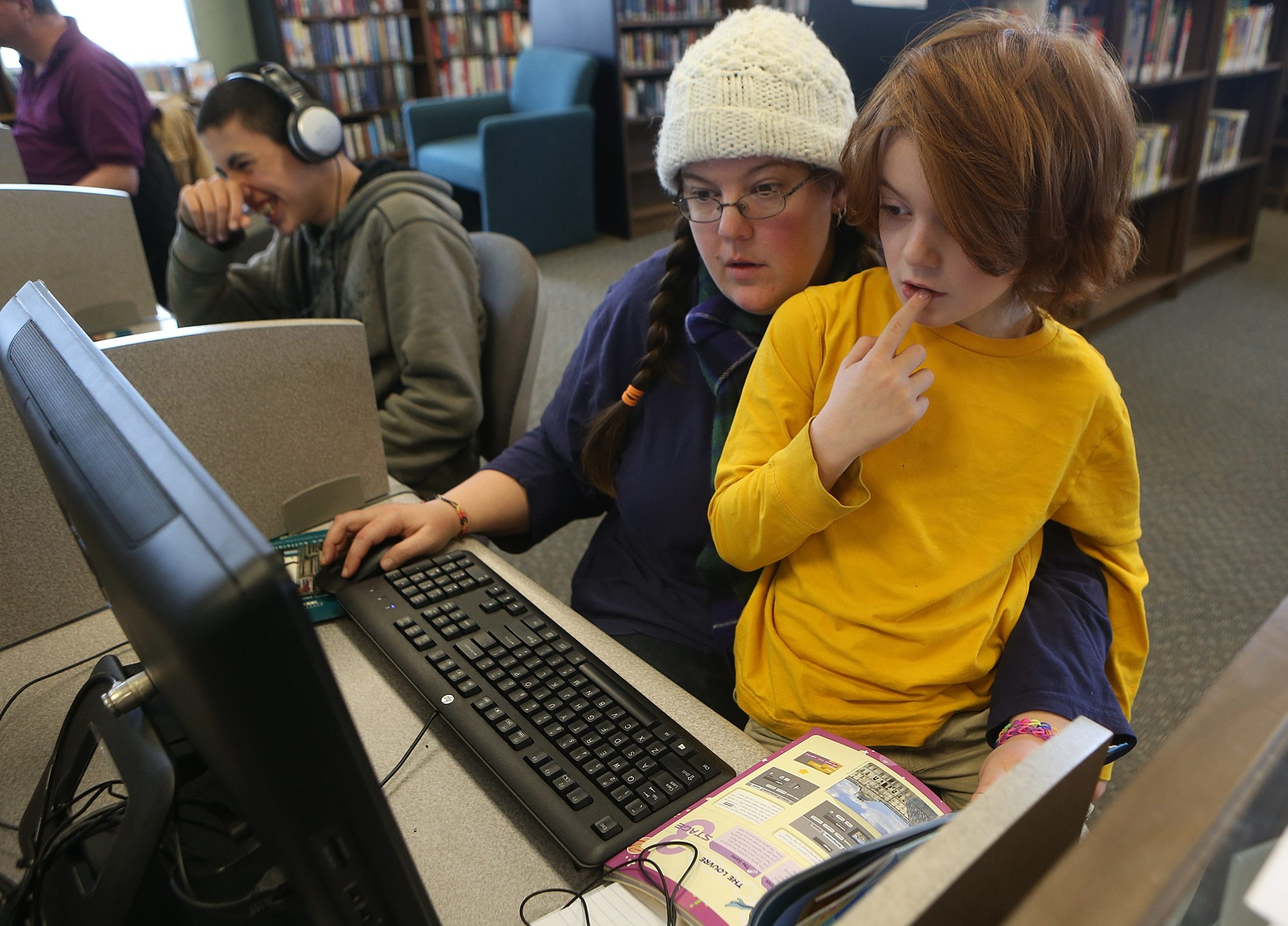 Home-schooling mom Jennifer Balazadeh helps her son,  Machias, 7, with a lesson on a computer at the North Collins Public Library on Sunday.