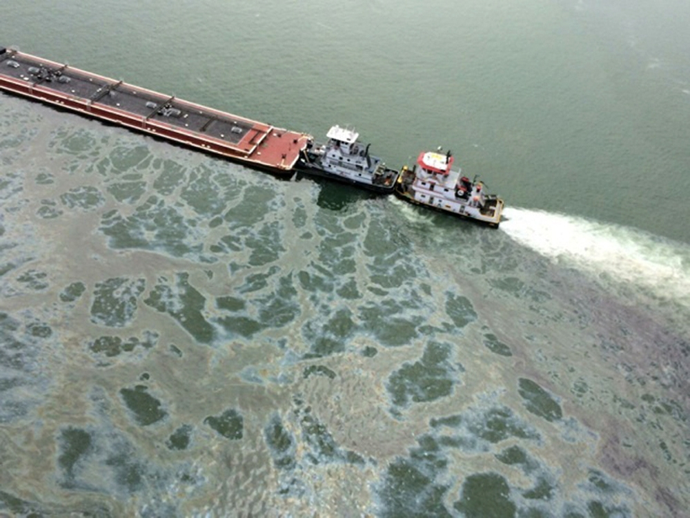 Oil spews from a barge loaded with marine fuel oil after the barge collided with a ship in the Houston Ship Channel on Saturday. Some 168,000 gallons of the thick oil leaked into Galveston Bay.
