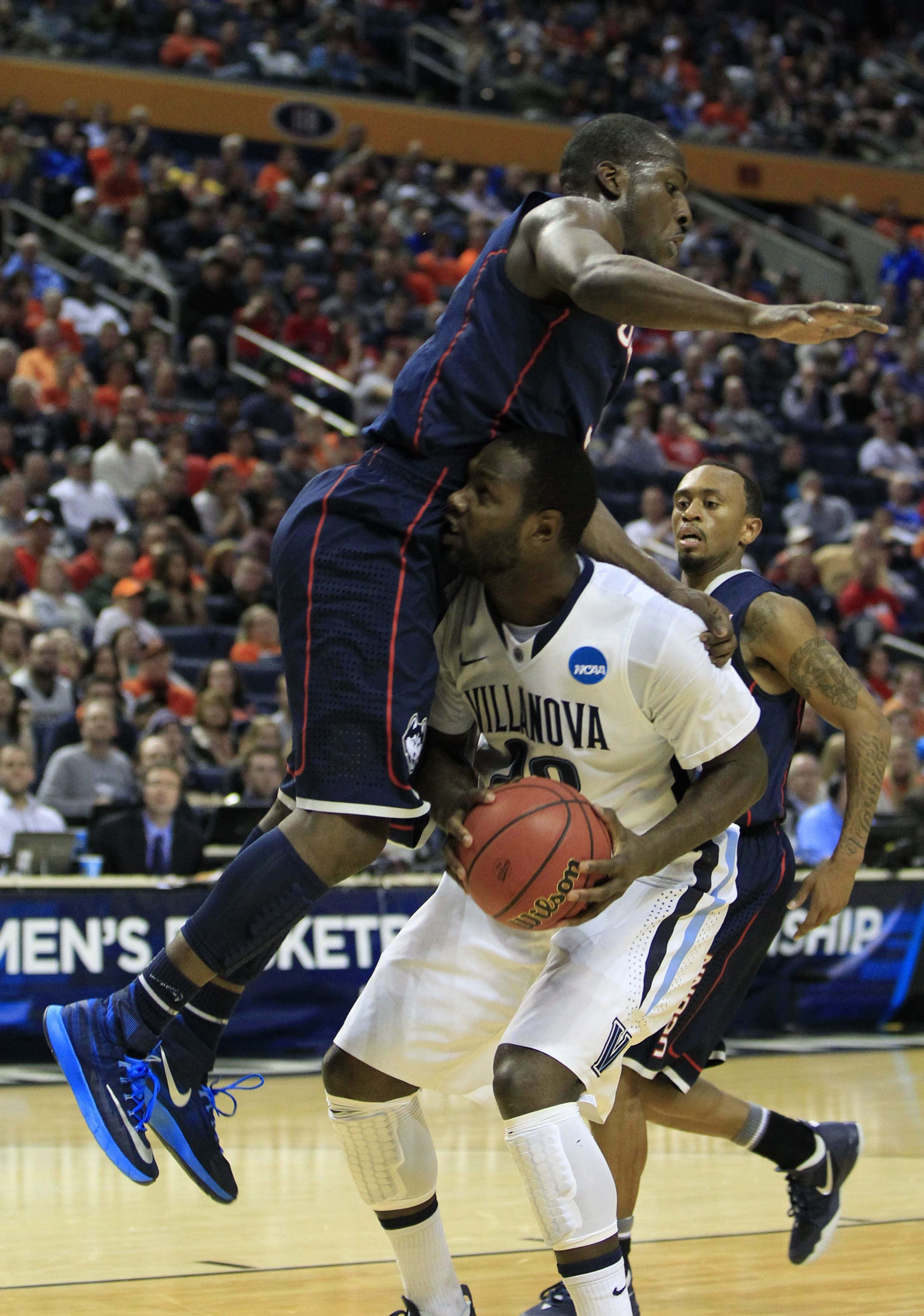 Villanova's JayVaughn Pinkston (22) is fouled by UConn's Terrence Samuel (3) during the first half of their third-round game at the First Niagara Center on Saturday.