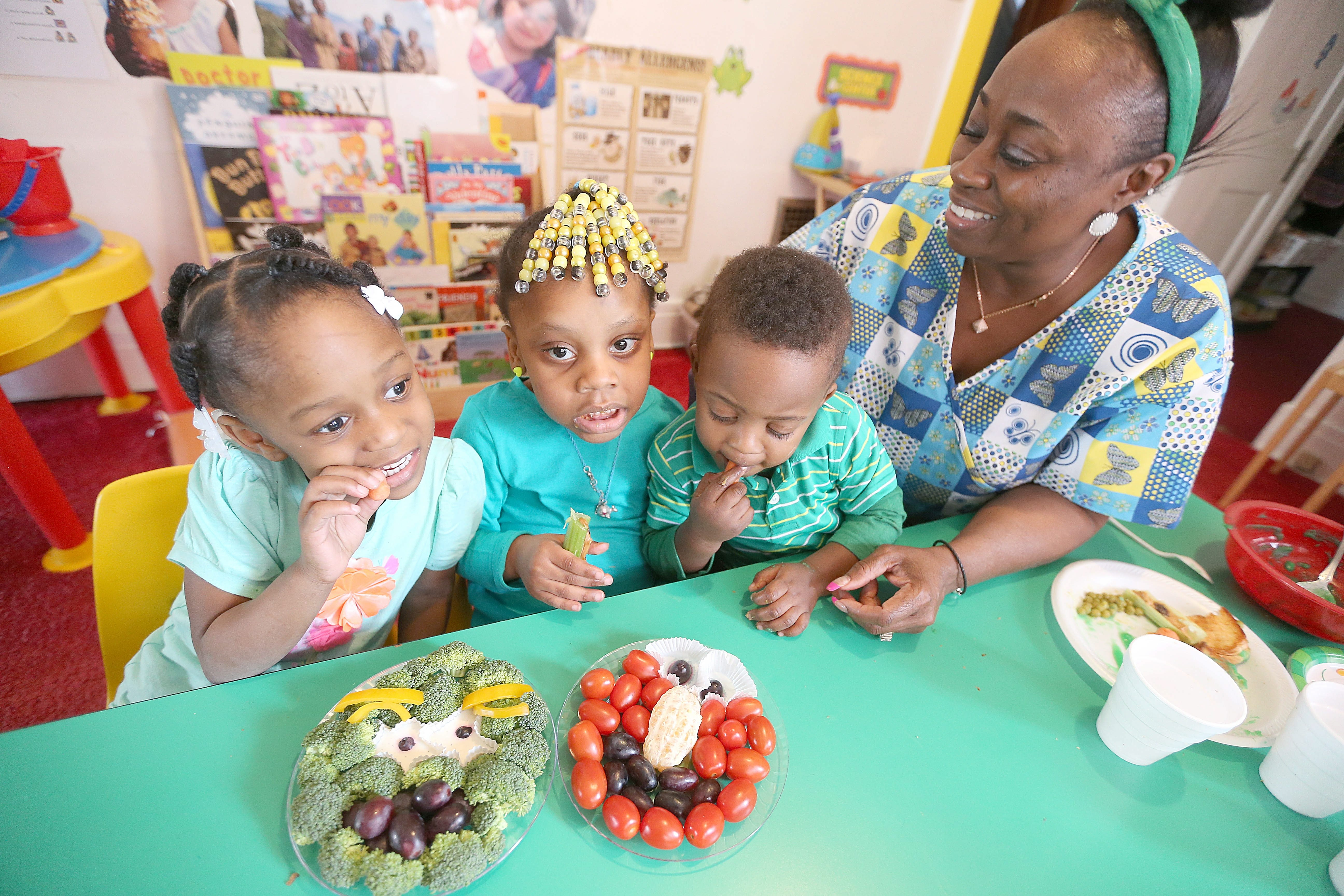 From left, Kennedy Jackson, 4, Trinity Simmons, 3, and Josiah Hutchinson, 2, munch on healthy snacks with Renee Benning at Something Special Day Care in the University District.