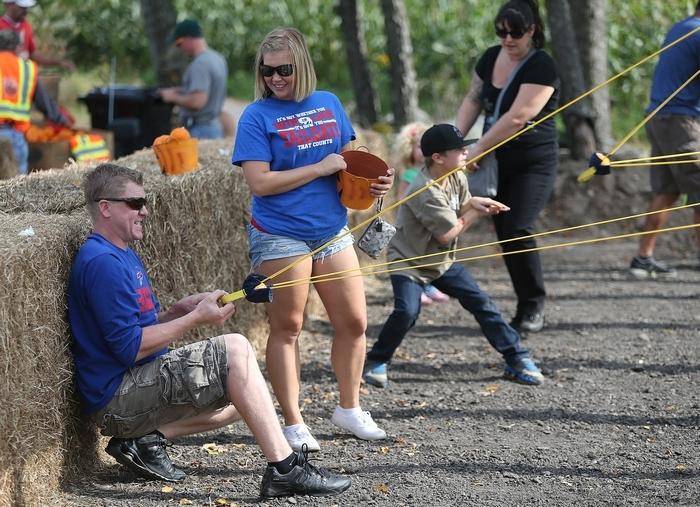Eric Rejman pulls back the pumpkin slingshot, preparing to release a mini pumpkin, as his girlfriend, Kelly Kubala, coaches him at the Great Pumpkin Farm on Sunday. (Robert Kirkham/Buffalo News)