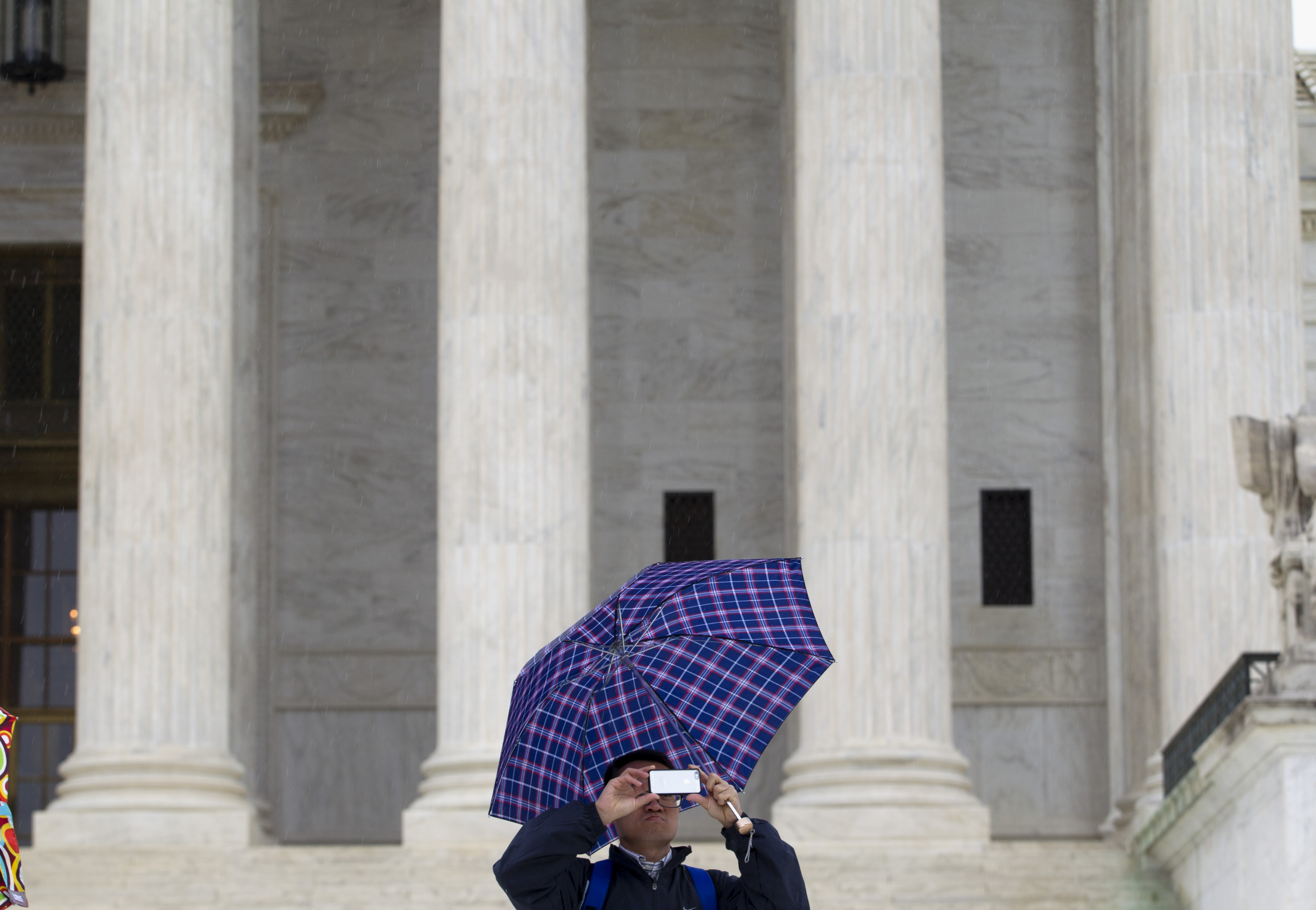A Supreme Court visitor takes pictures with his cell phone outside the Supreme Court in Washington, D.C., Tuesday.