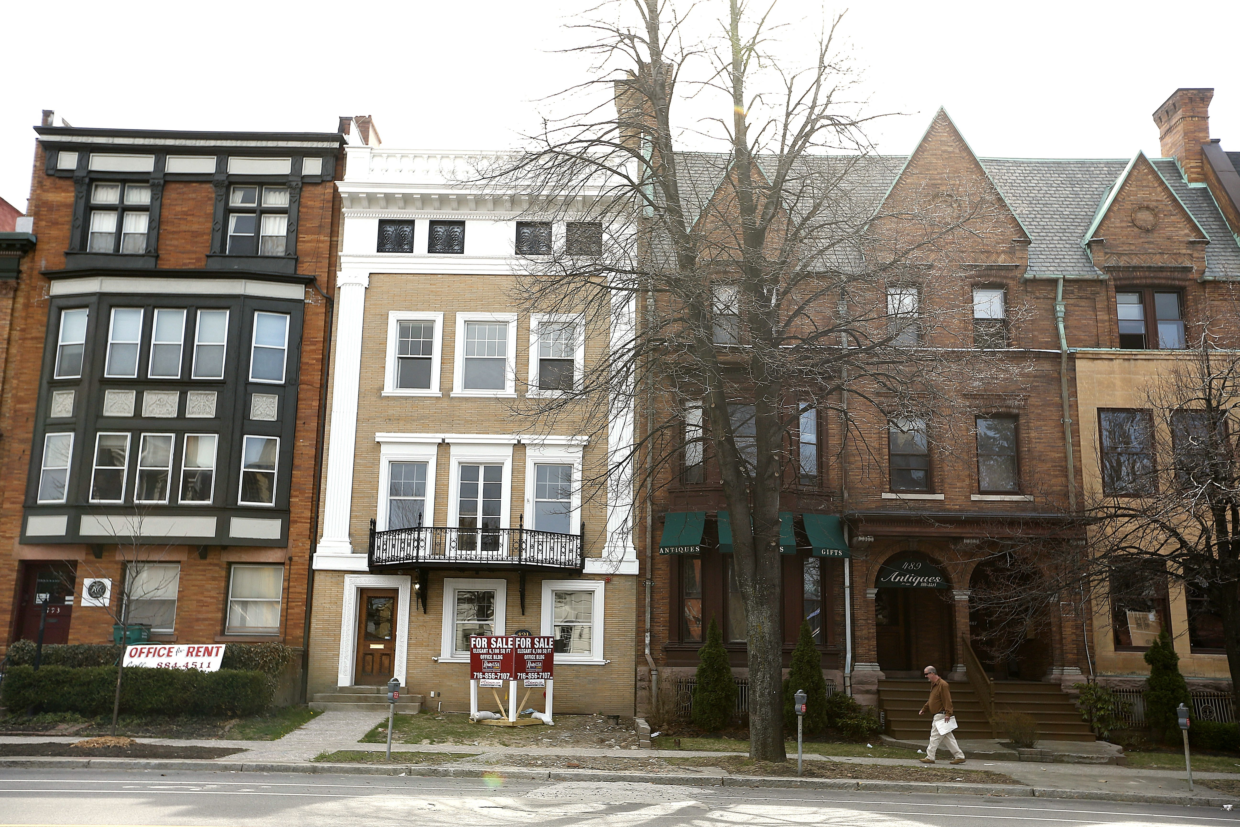 """With a """"For Sale"""" sign on its lawn, the brownstone at 491 Delaware Ave. has been completely renovated."""