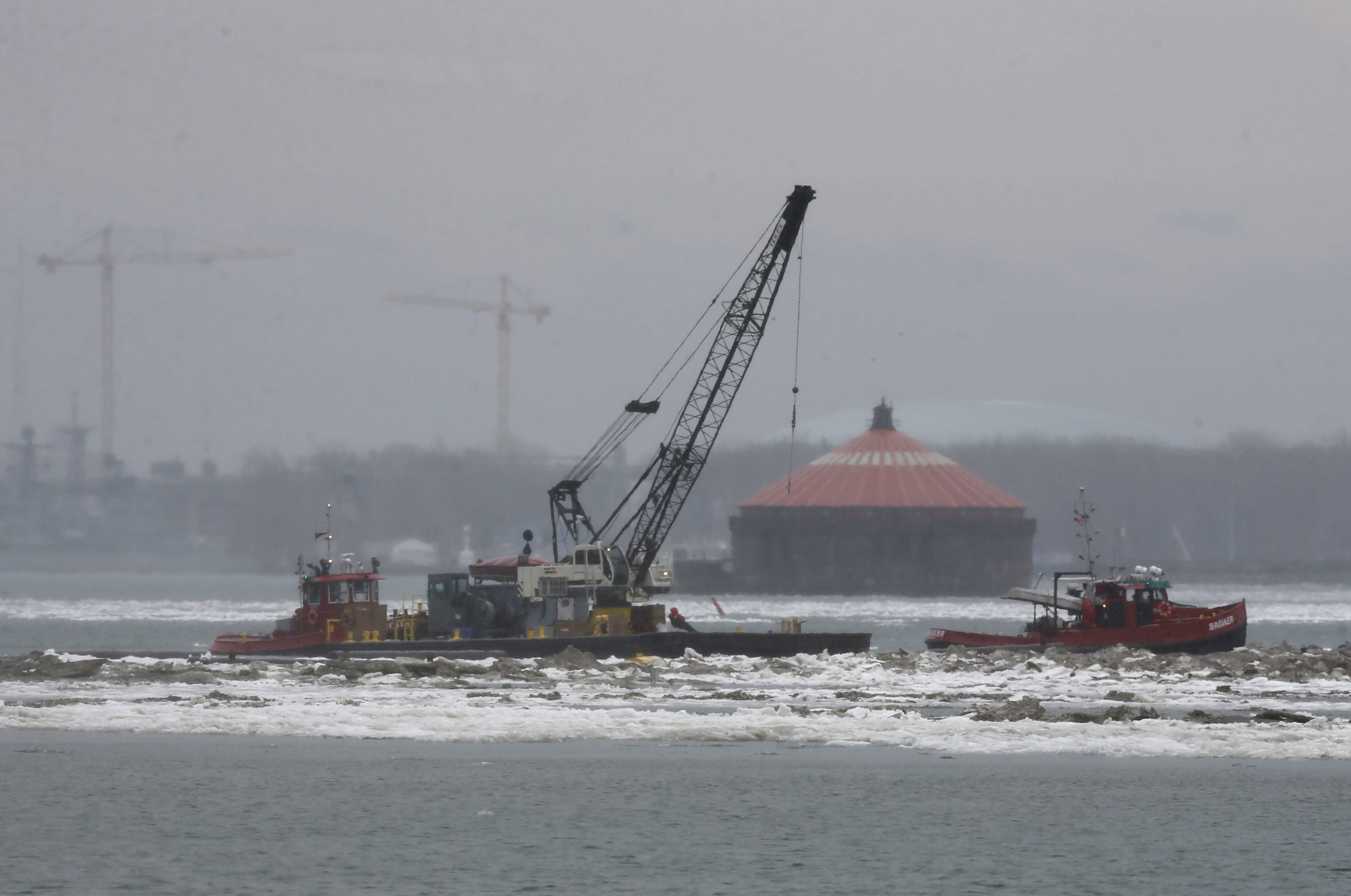 New York Power Authority workers use a barge, the tug JonCaire, left, and an ice breaker vessel to begin removing the ice boom from Lake Erie on Tuesday.