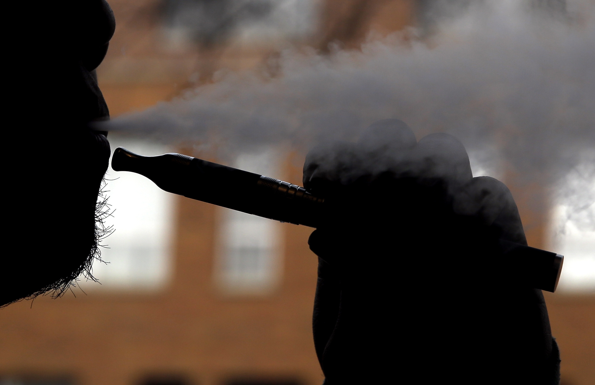 Daryl Cura demonstrates an e-cigarette at Vape store in Chicago, Wednesday. The federal government wants to ban sales of electronic cigarettes to minors and require approval for new products and health warning labels under regulations being proposed by the Food and Drug Administration. (Associated Press photo)
