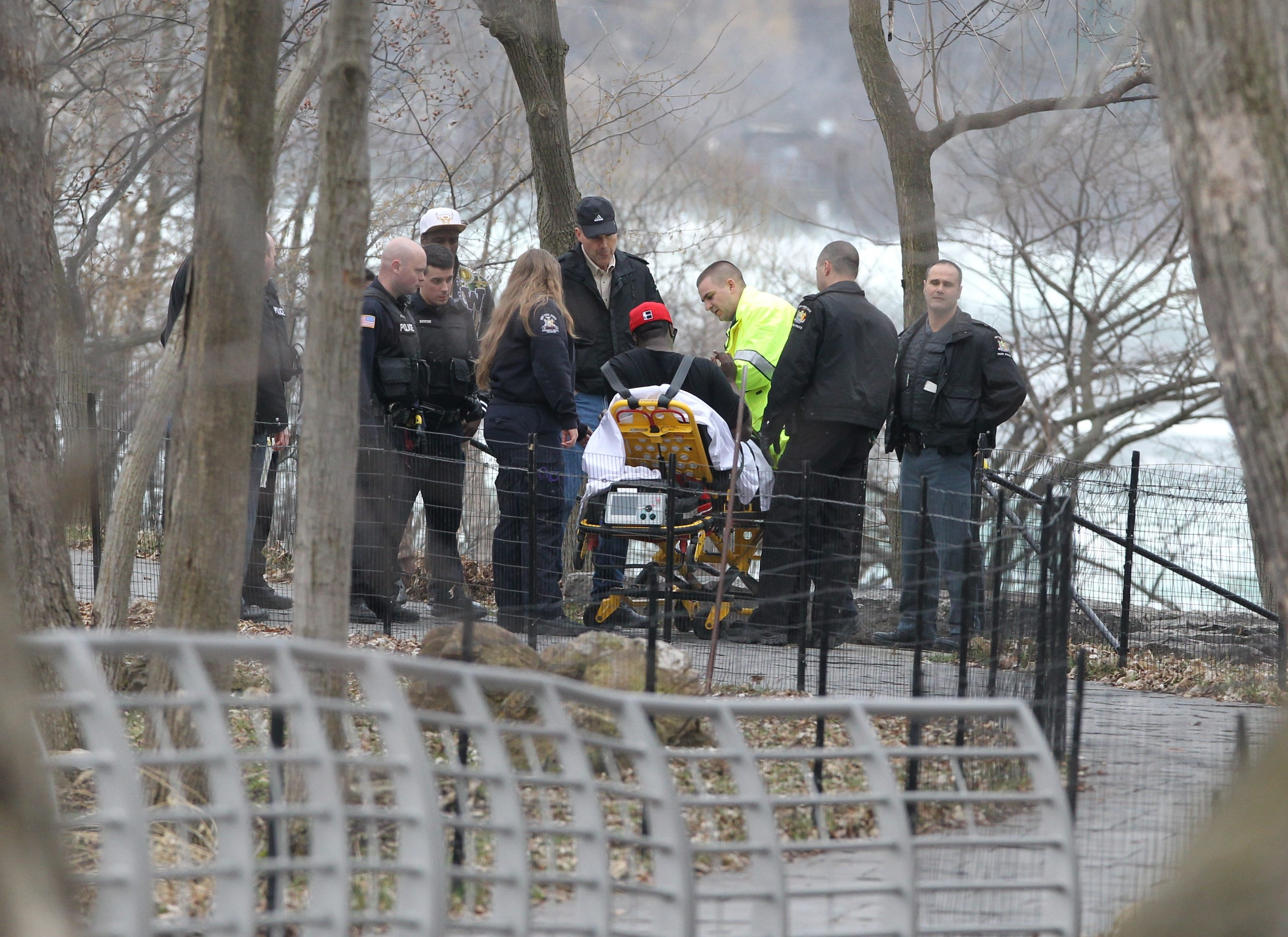 A man who waded into the Niagara River off Three Sisters Islands on Saturday is wheeled to an ambulance.