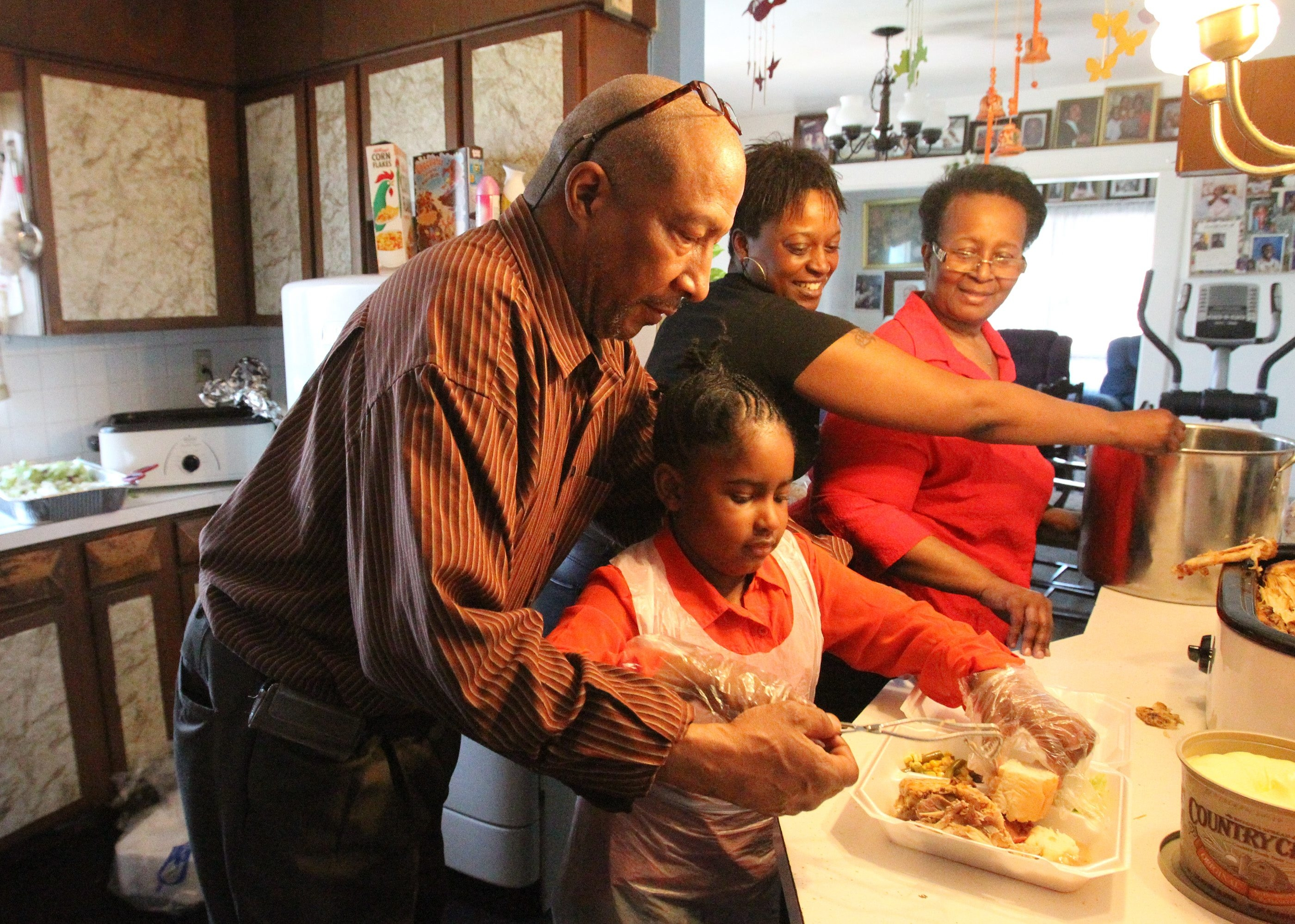 Matthew Davis and his granddaughter, Zioanna Carter, his daughter, Tishnell Davis, and his wife, Yvonne Davis, prepare Easter dinner for the needy in Niagara Falls.