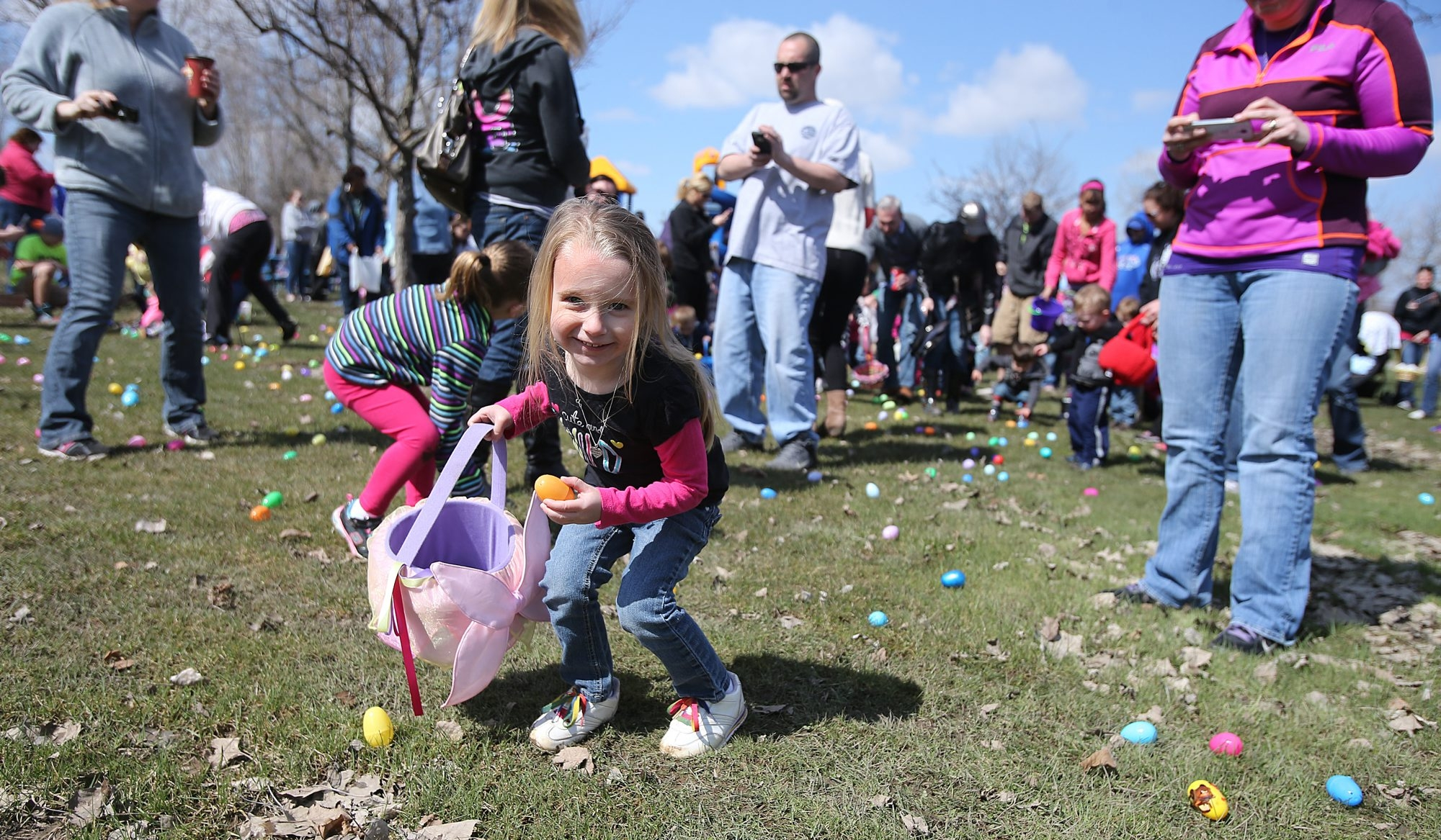 Tayen Perkins, 3, of West Seneca, gets ready to scoop up Easter eggs in Harlem Road Park in West Seneca on Saturday. It was a cool but brilliantly sunny day, perfect for discovering spring treasures.
