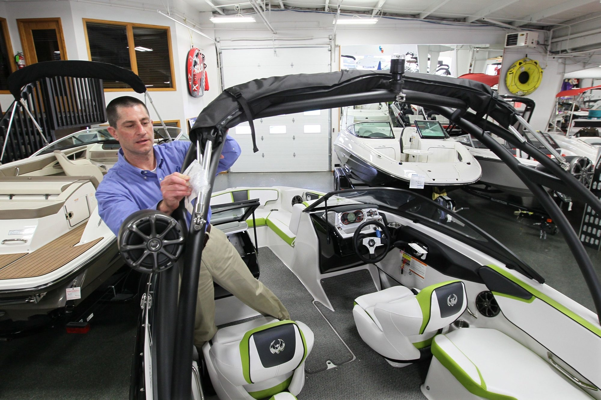 Todd Riepe, of SkipperBud's, gets a Scarab jet boat ready for sale, April 8, 2014, in Pewaukee, Wis. Boats that use a jet drive instead of propeller are becoming more popular. (Michael Sears/Milwaukee Journal Sentinel/MCT)