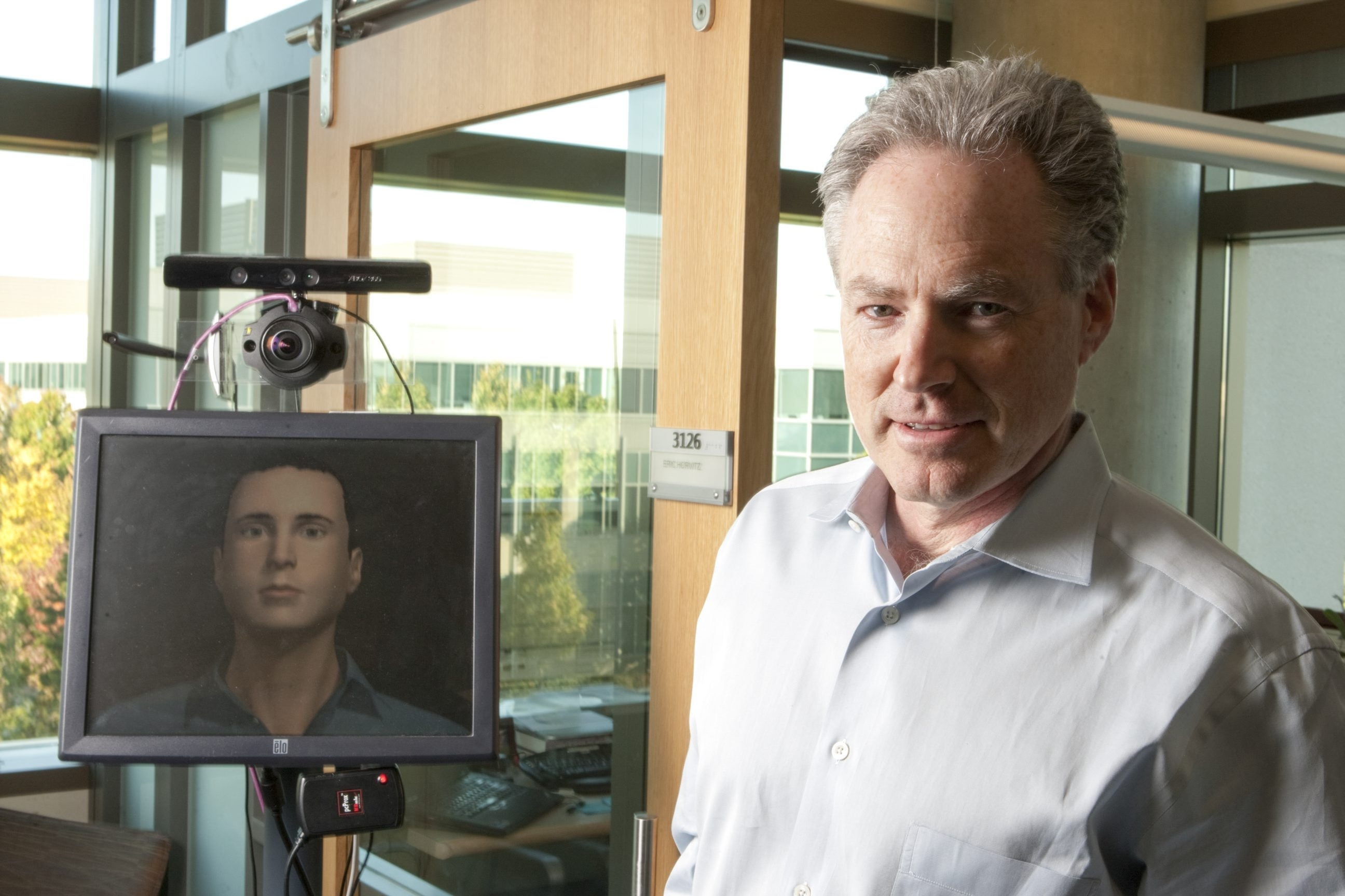 FILE -- Eric Horvitz, co-director of Microsoft Research, stands next to a robot in his office in Redmond, Wash., Oct. 3, 2012. A modern spin on age-old Luddite fears has crept into our understanding of technological innovations, as information technology creeps into occupations that have historically relied on brainpower and threaten to wreak havoc on the job market. (Kevin P. Casey/The New York Times)