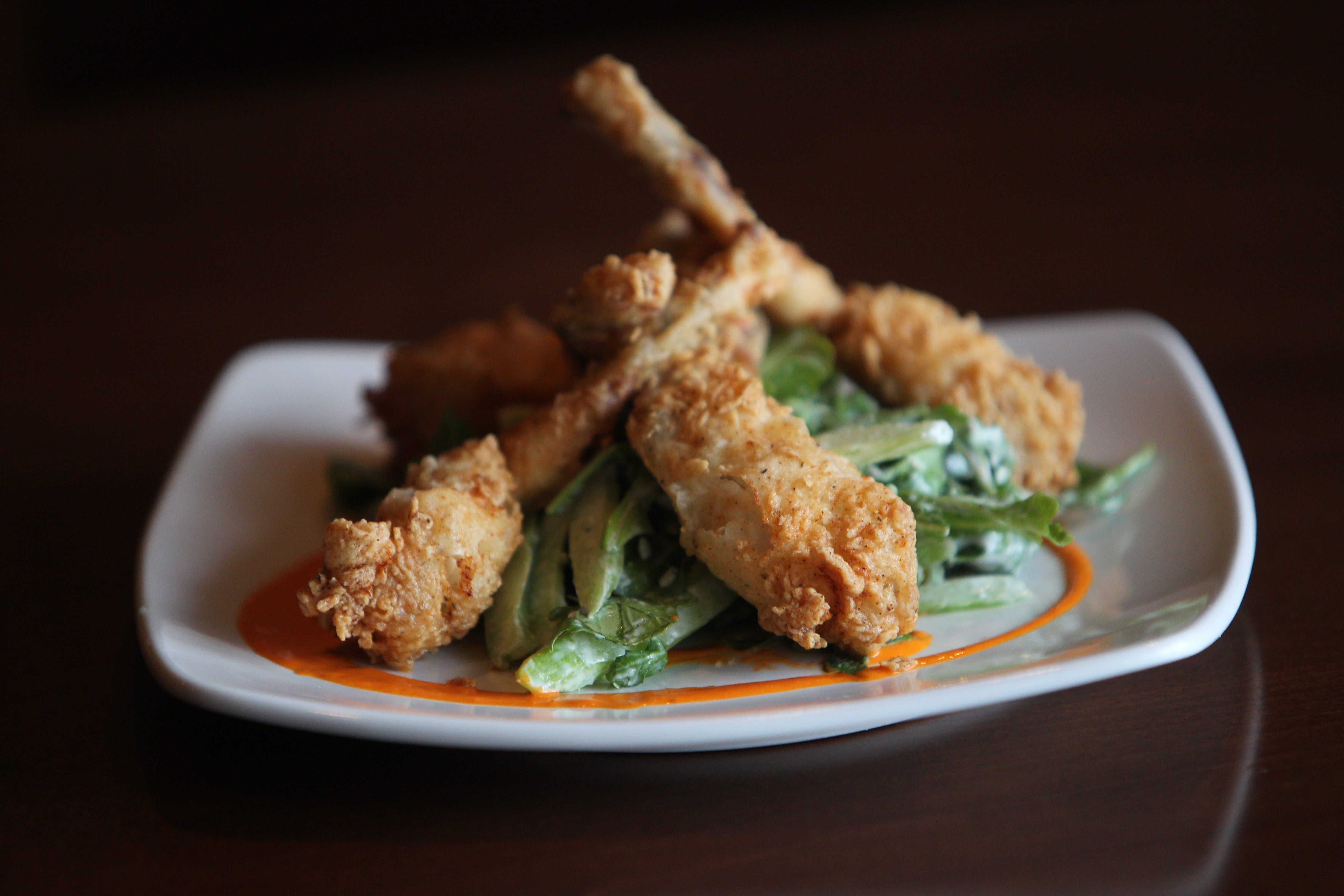 The frog legs at Mericana are flour-crusted, fried and served on celery hearts in buttermilk dressing. (Sharon Cantillon/Buffalo News)