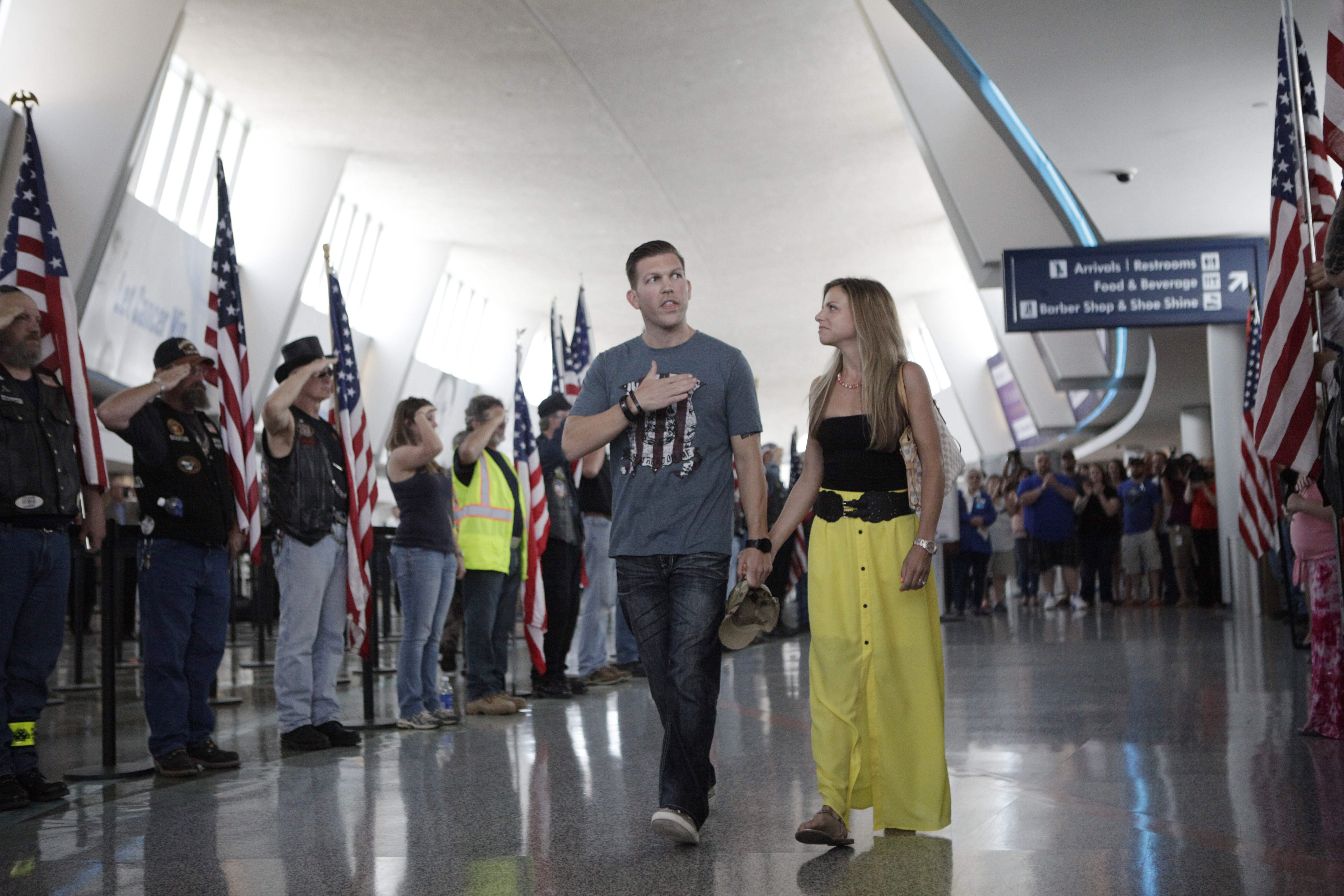 Maj. Patrick Miller and his wife, Ashley, walk through a row of Patriot Guard Riders and supporters holding flags after arriving Friday at Buffalo Niagara International Airport.
