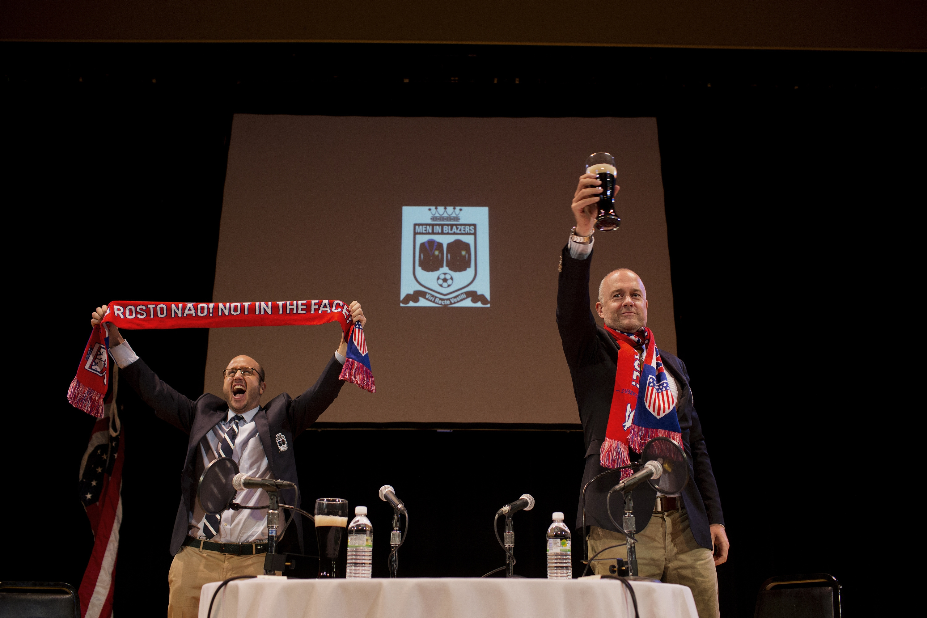 Michael Davies, right, and Roger Bennett, hosts of ESPN's 'Men in Blazers,' arrive on stage for a live show in New York, May 30, 2014. The soccer podcast hosts have taken their amusing riffing mainstream now that the World Cup is dominating the U.S. sports conversation. (Victor J. Blue/The New York Times)