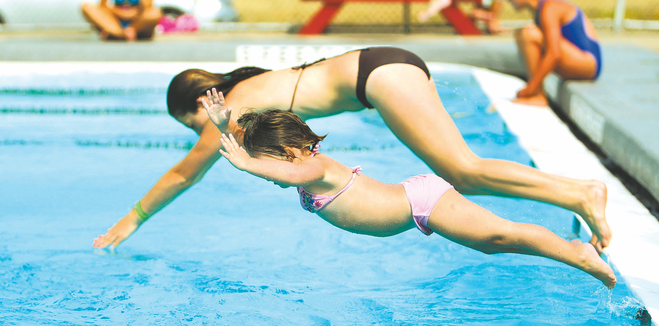 Jessica Jaskowiak, 13, and Josefina Yanosh, 3, dive into the water simultaneously at the Lincoln Pool in the Town of Tonawanda in this file photo from July 17, 2012.