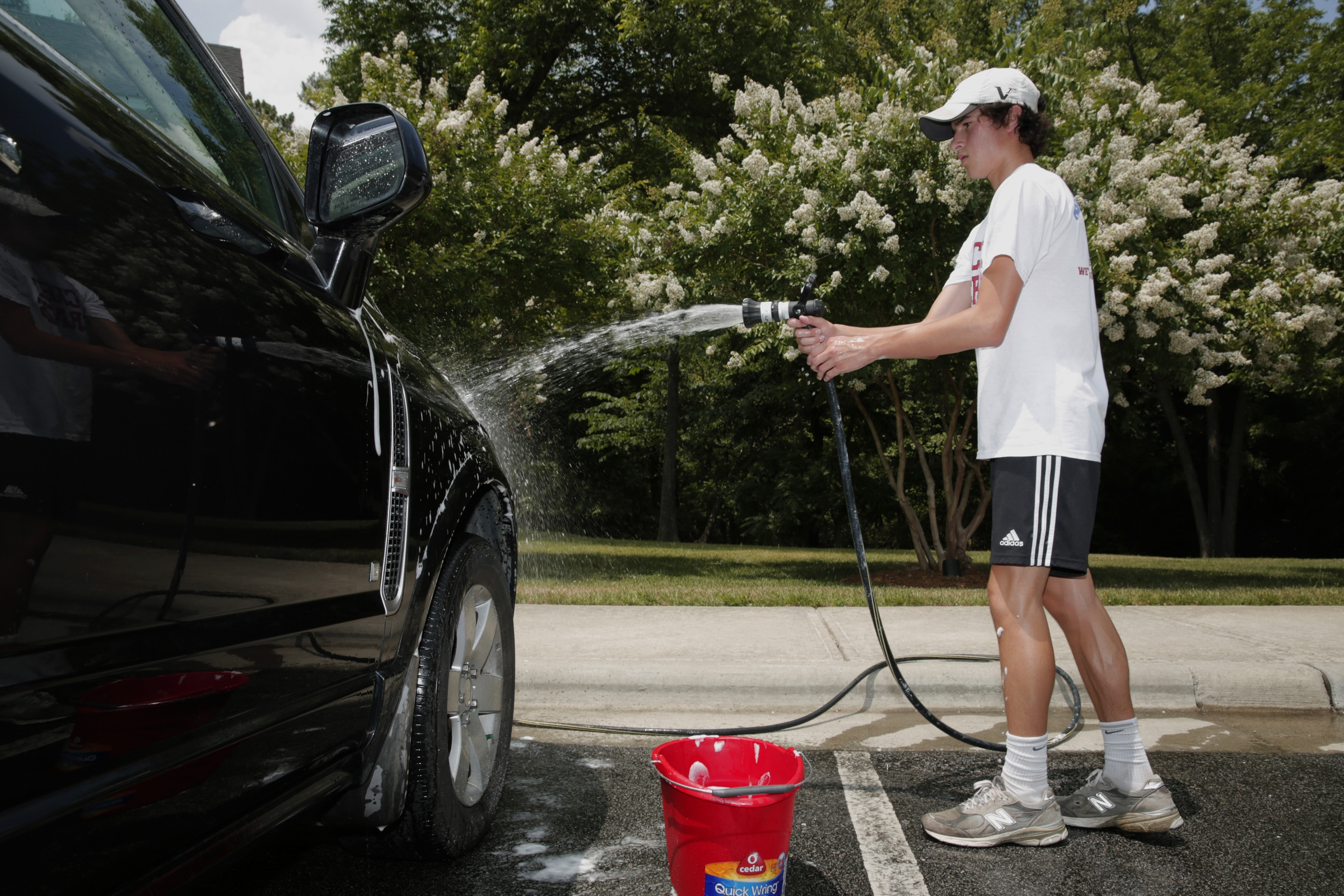 "Hunter-John Hurst, 16, of Holly Springs, N.C., washes a car as part of a detailing service he started after having trouble finding a summer job. He charges $35 to $45 for an hour's work per vehicle, ""and I can make more money than I would at a regular job."""