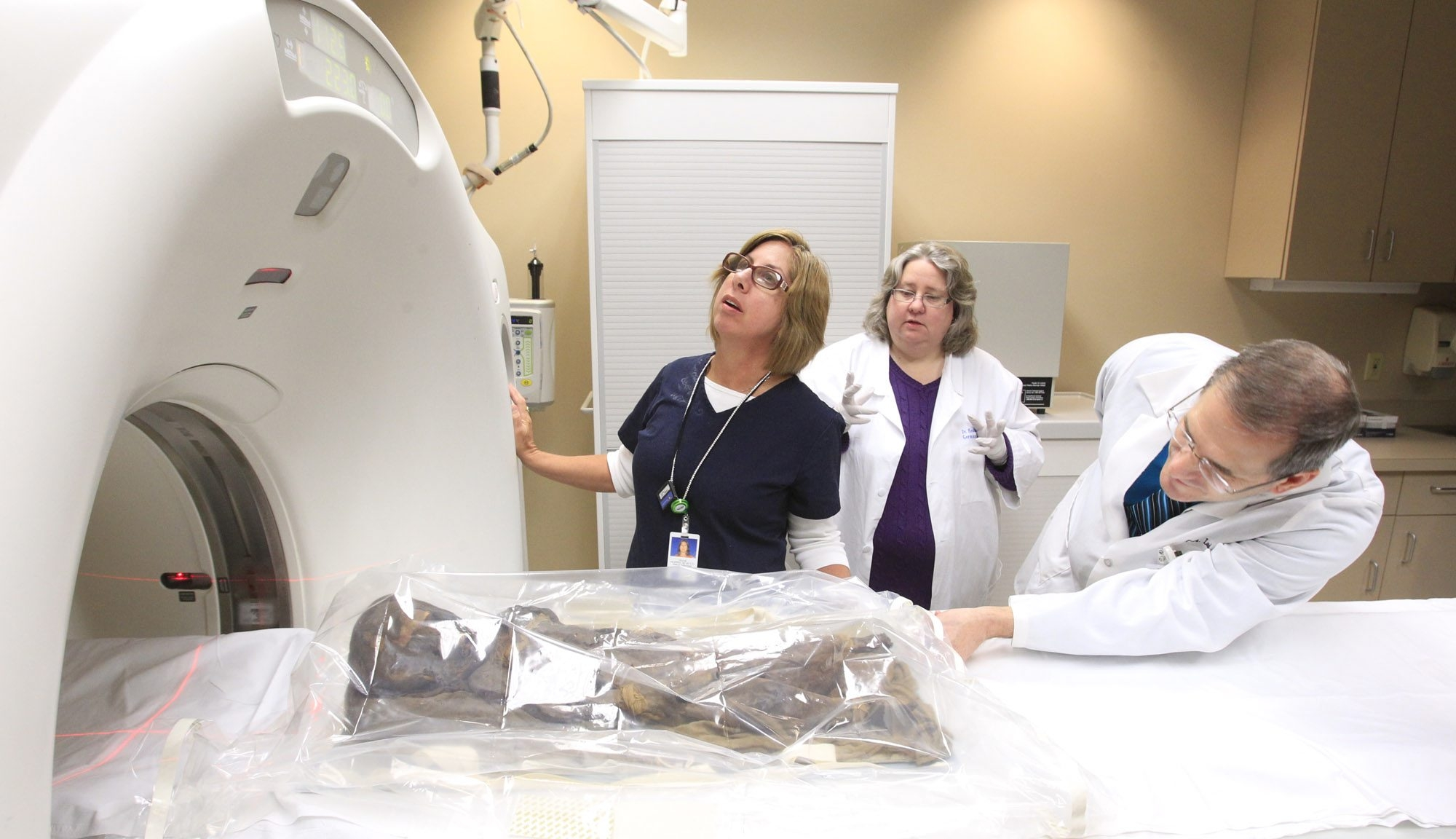 Dr. Heather Gill-Ferking of the Buffalo Museum of Science, center, and Roswell Park Cancer Institute's Diane Filippini and Dr. Peter Loud prepare a mummy for a CT scan.
