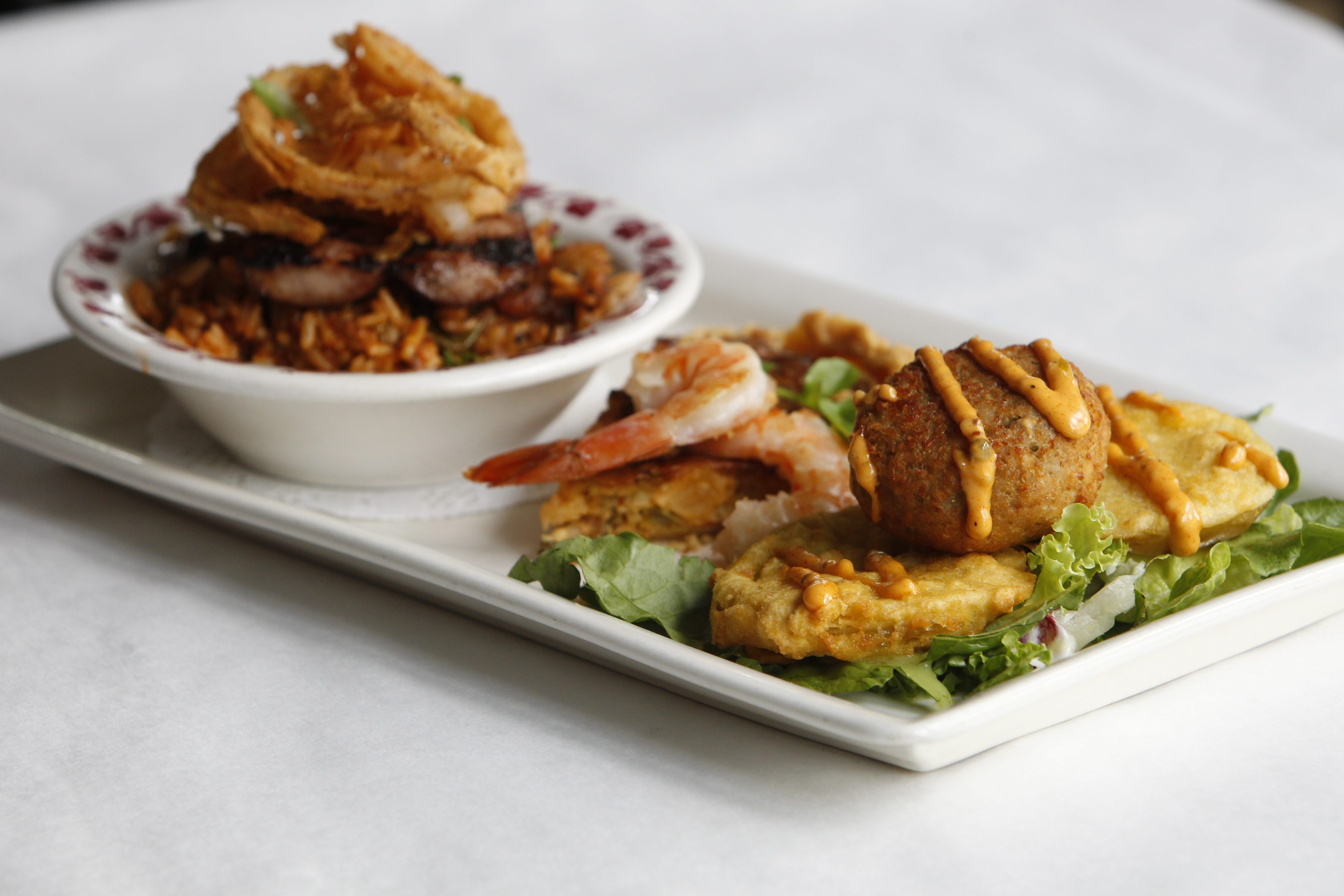 From left, jambalaya with grilled Polish sausage and onion rings; lobster cheesecake with shrimp; and crab cake over fried green tomatoes.