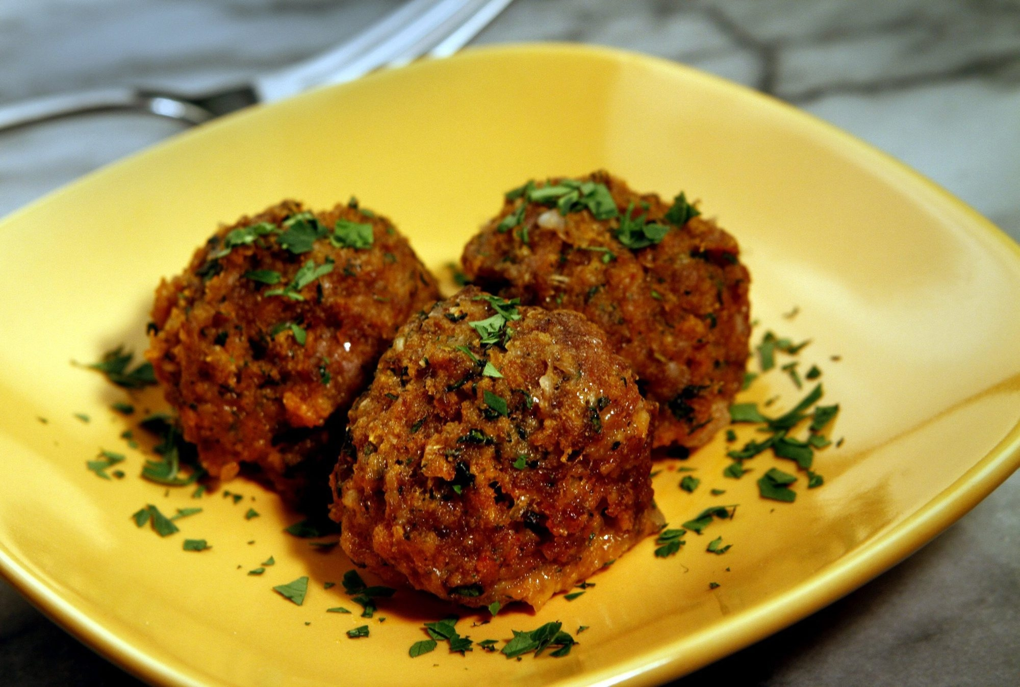Roasted garlic, fresh basil and cilantro, along with dried oregano, Spanish paprika and grated Manchego cheese lend rich, deep flavor to these tender pork-and-beef meatballs served at Cafe Sevilla in Riverside, Calif.