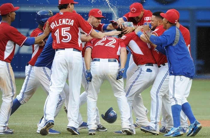 Toronto Blue Jays' Jose Bautista celebrates with teammates after hitting a walk off single against the Detroit Tigers during the 19th inning in Toronto on Sunday, the longest game in Blue Jays history. (AP Photo/The Canadian Press, Jon Blacker)