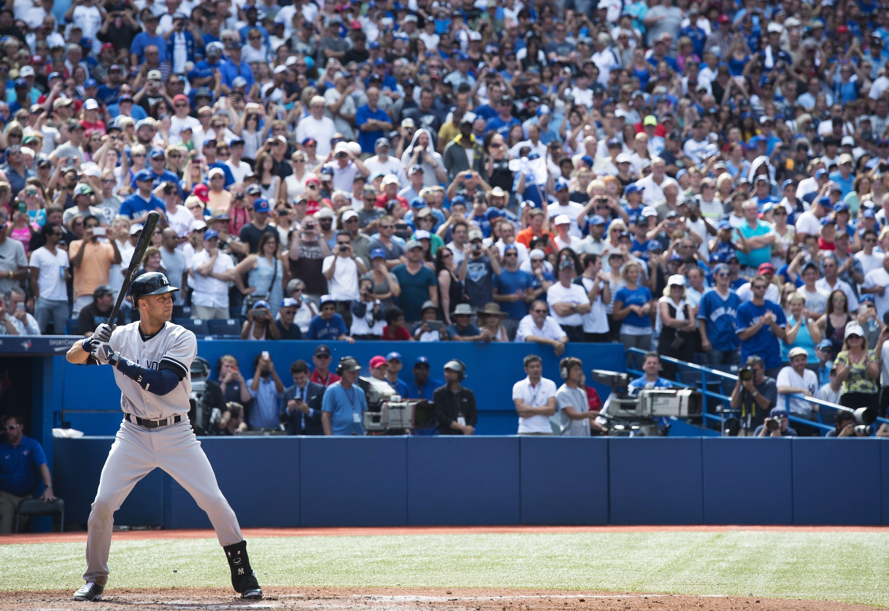 Fans stand in tribute as the Yankees' Derek Jeter takes his last Toronto at-bat against the Blue Jays in the ninth inning Sunday at the Rogers Centre.