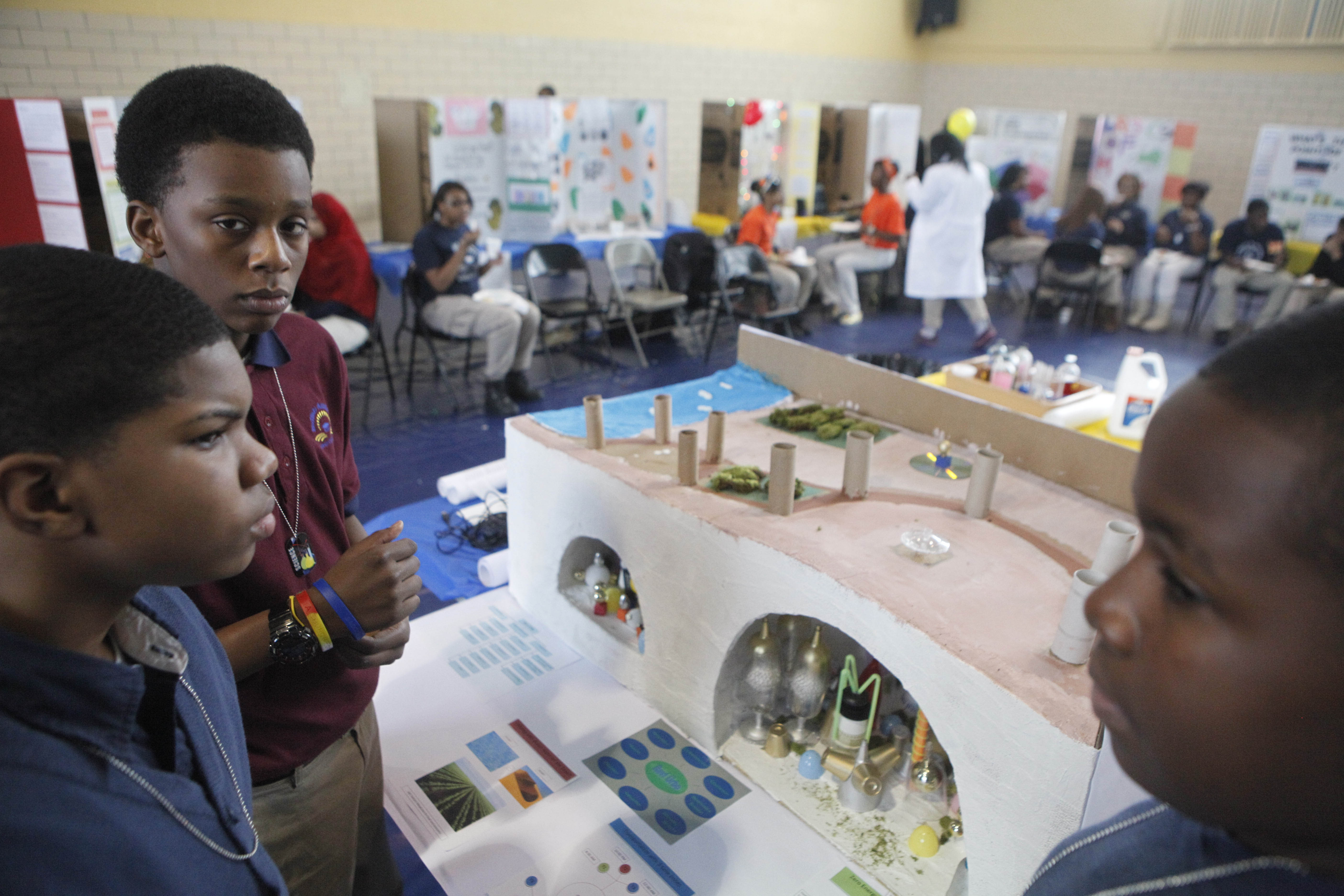 In this 2012 photo, eighth-graders Miles Glenn, Lauren Killian and Matthew Jeffries explain the model city they built for the annual Science Fair at the Buffalo Academy of Science Charter School. Their city, dubbed Revi Urbo, was a zero-energy, self-sustaining community built underground in the desert.