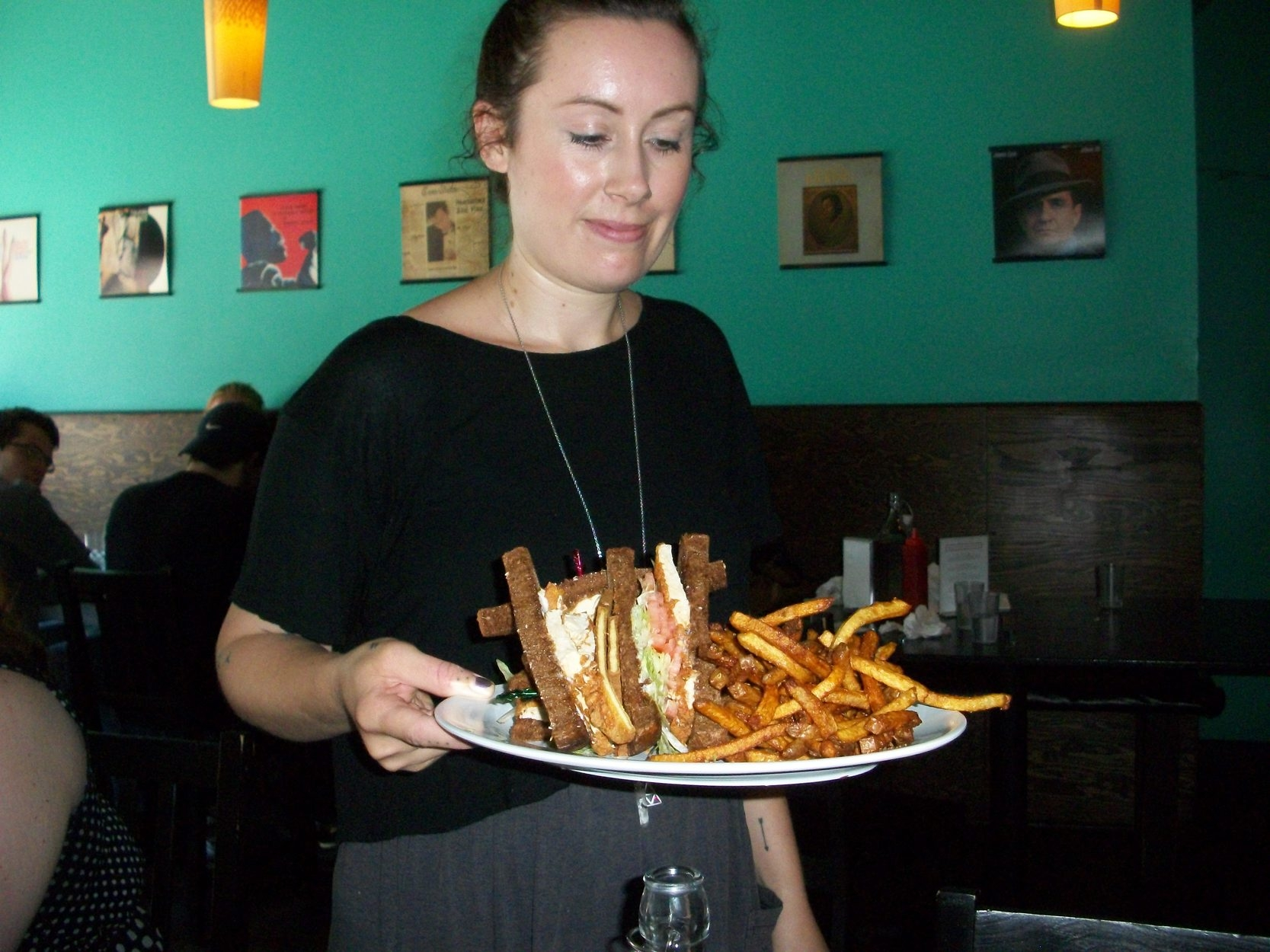 """A waitress at Hogtown Vegan, one of many Toronto area vegetarian restaurants, serves the Unchicken Club Sandwich, complete with french fries."""""""