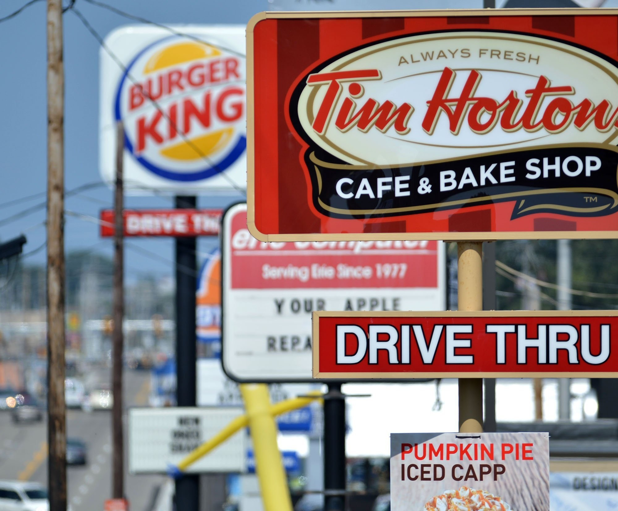 Signs for a Tim Hortons restaurant, foreground, and a Burger King restaurant are displayed along Peach Street in Erie, Pa. Berkshire Hathaway announced Tuesday that it will provide financing for Burger King's deal to buy Tim Hortons.