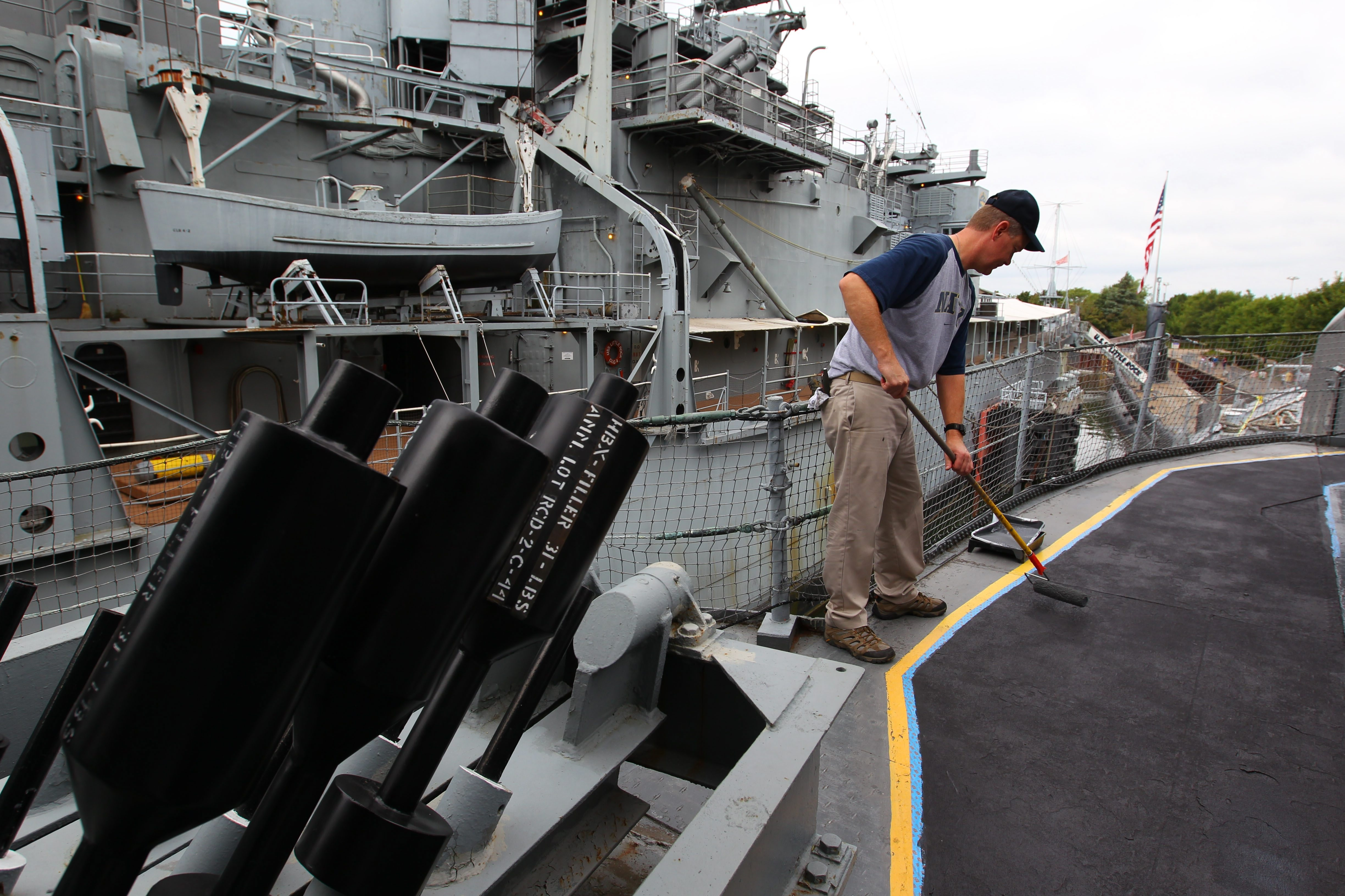 Paul Lester of Orchard Park, one of the Tin Can Sailors, paints a walkway on the USS The Sullivans on Saturday.