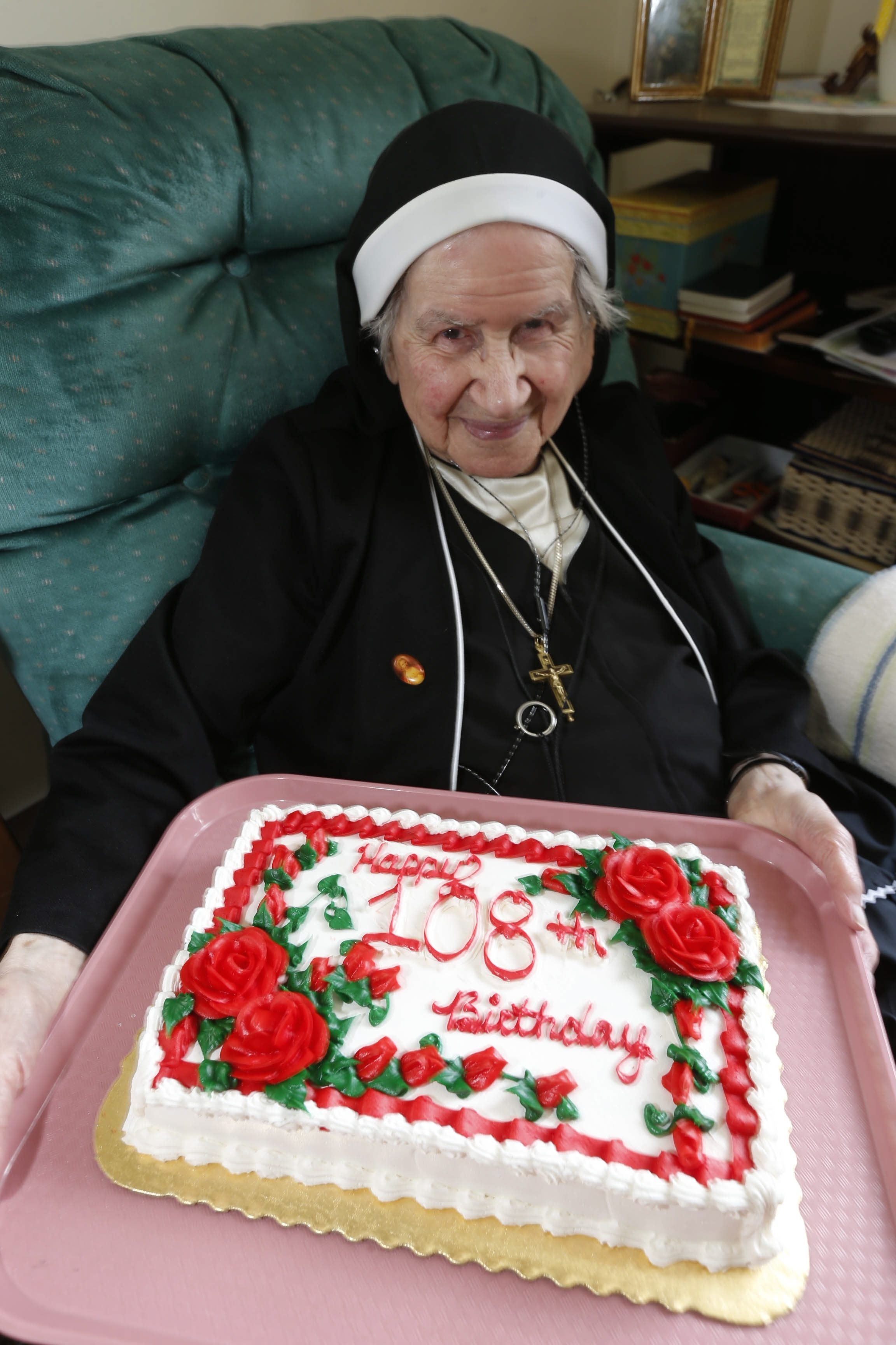 Sister John Maron Abdella admires the cake she was given to celebrate her 108th birthday at the Sisters of St. Joseph residence in Clarence on Friday.
