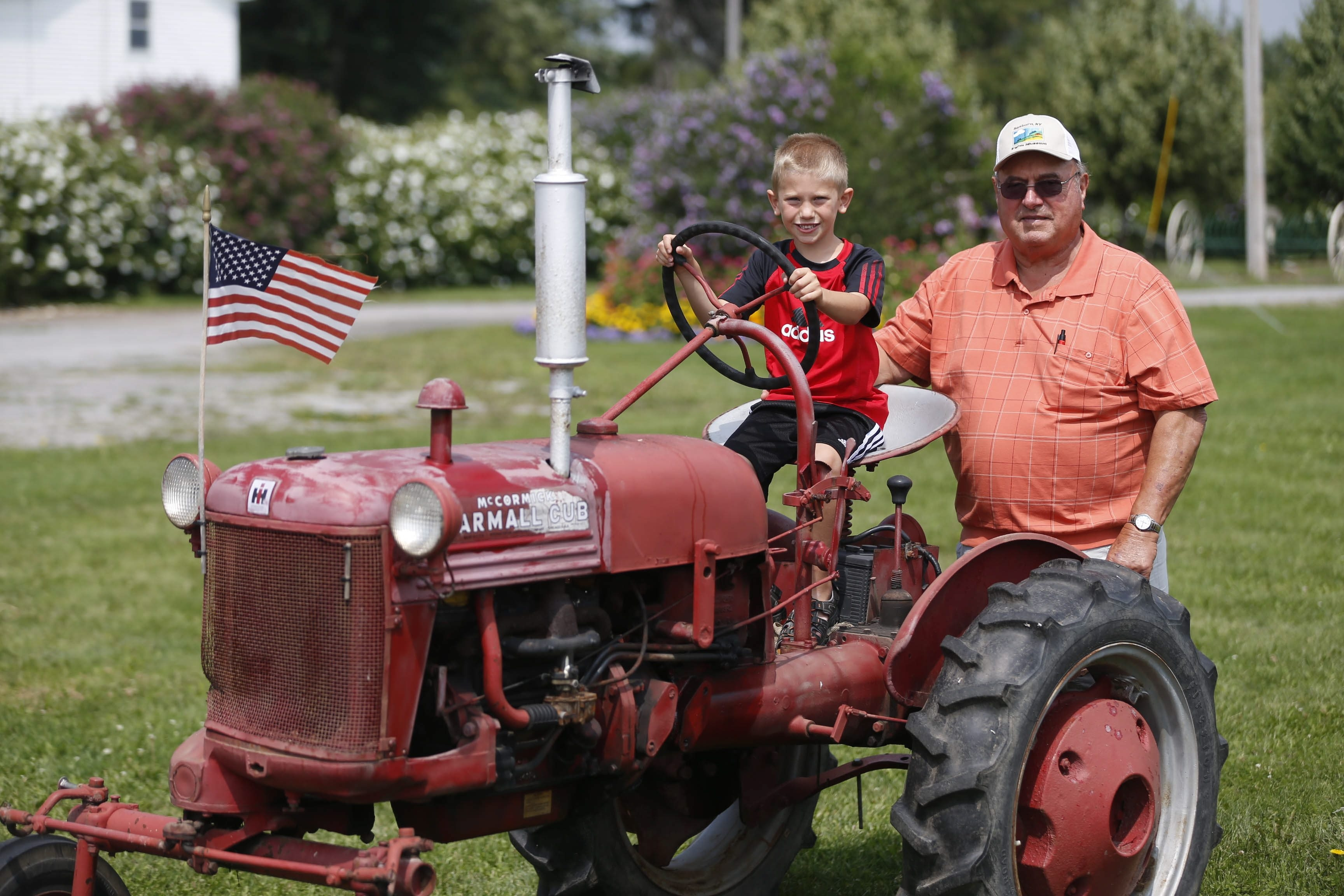 Gary Townsend with grandson Sammy Hoover, 6, on a tractor, at the Sanborn Area Historical Society campus.