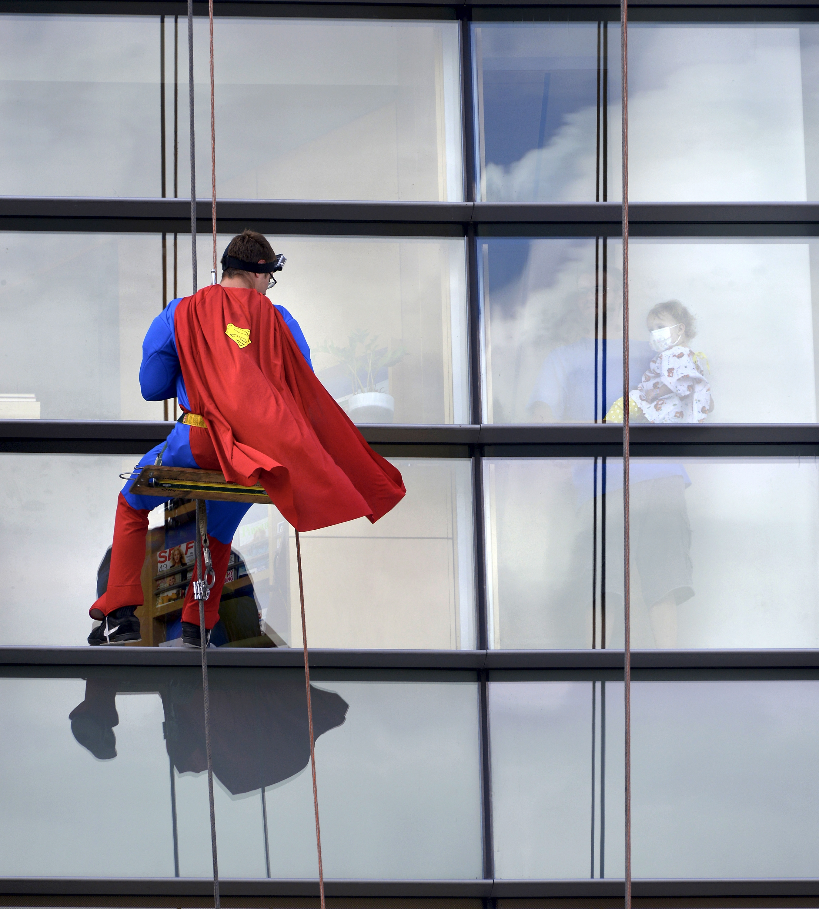 Super visitor: A young patient watches Superman rappel down  Hershey Children's Hospital Wednesday morning in Hershey, Pa. Four superhero window washers greeted patients.