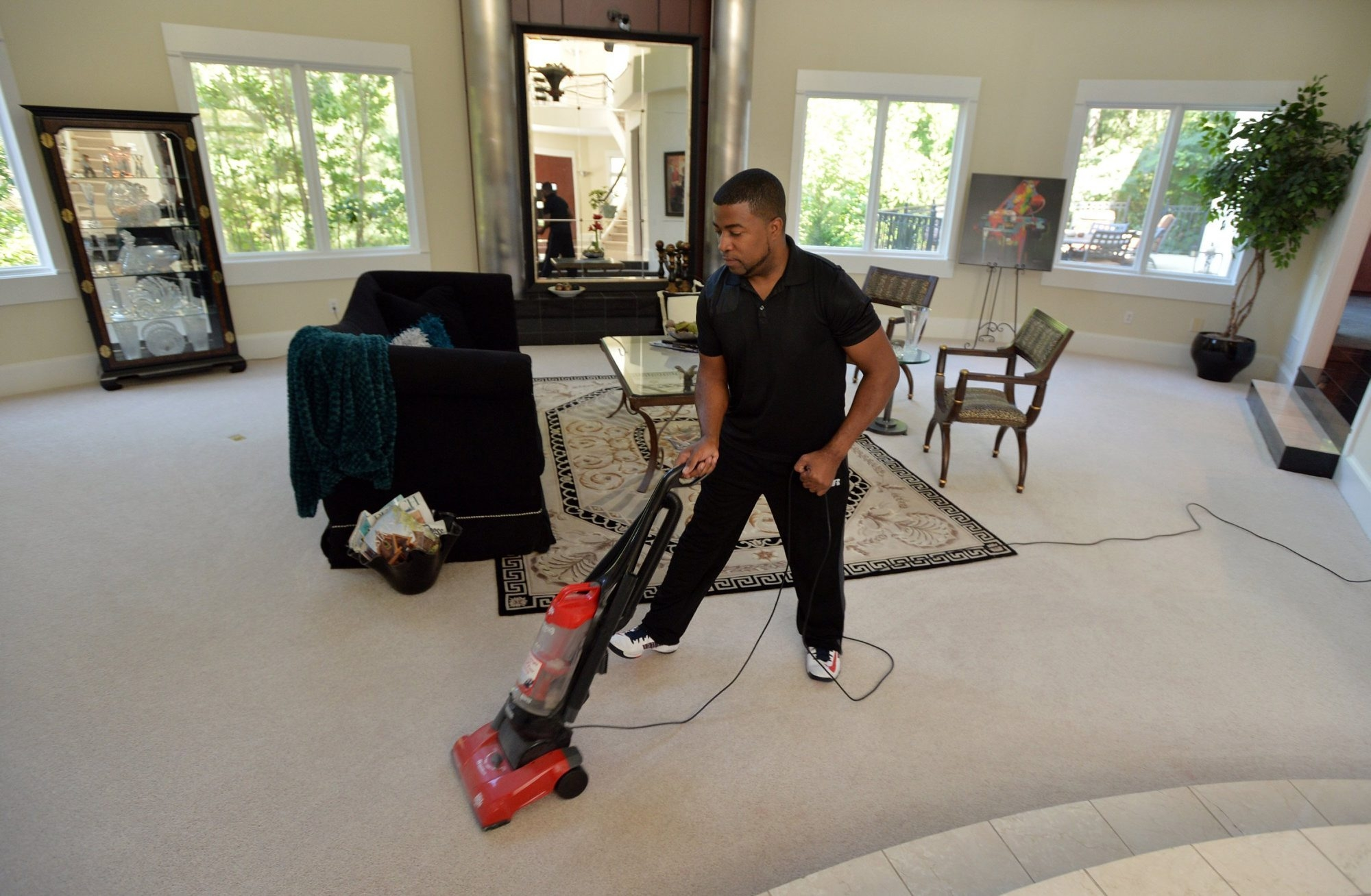 Craig Craft vacuums the carpet in a $1.6 million mansion July 29 in Atlanta. Craft and his roommate Eugene Sullivan are home managers, occupying vacant homes to give them a lived-in look.