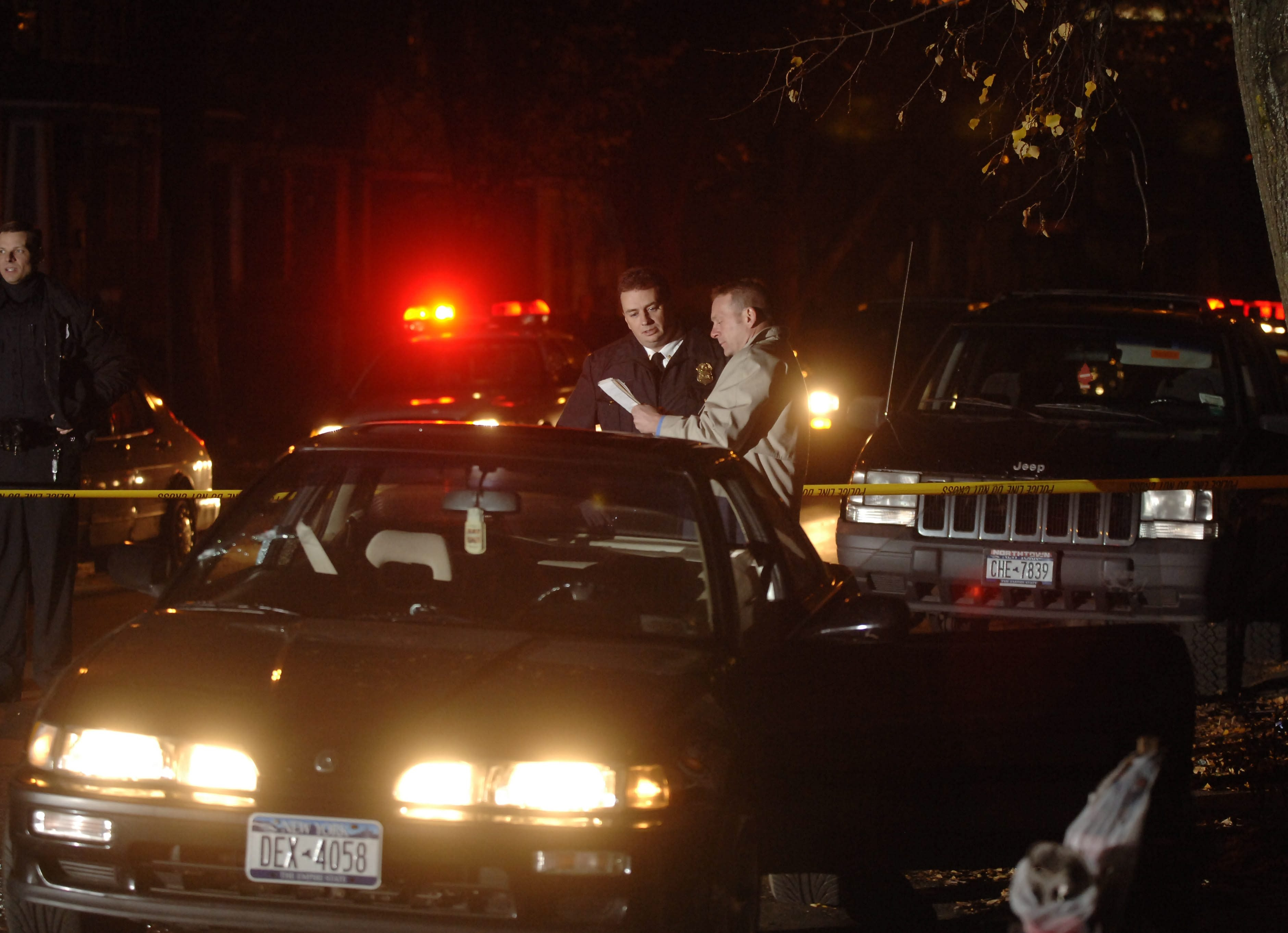 Buffalo Police investigate the scene of a drive-by shooting on Seventh Street in November 2005. For 10 years, two rival gangs battled on Buffalo's Lower West Side.