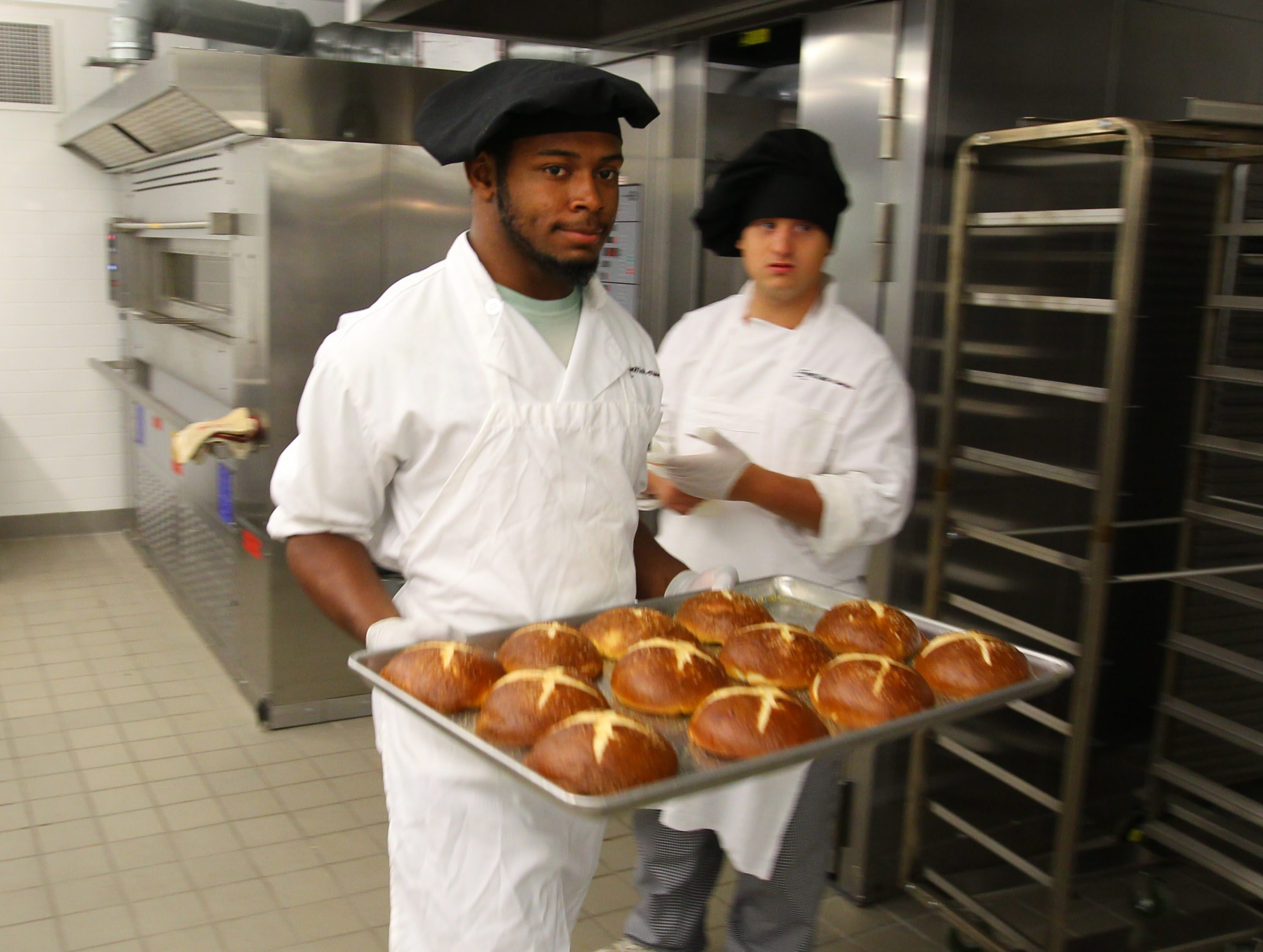 Keyon Hunley carries a tray of pretzel rolls at the Emerson School of Hospitality, the Buffalo school district's premier career education program.