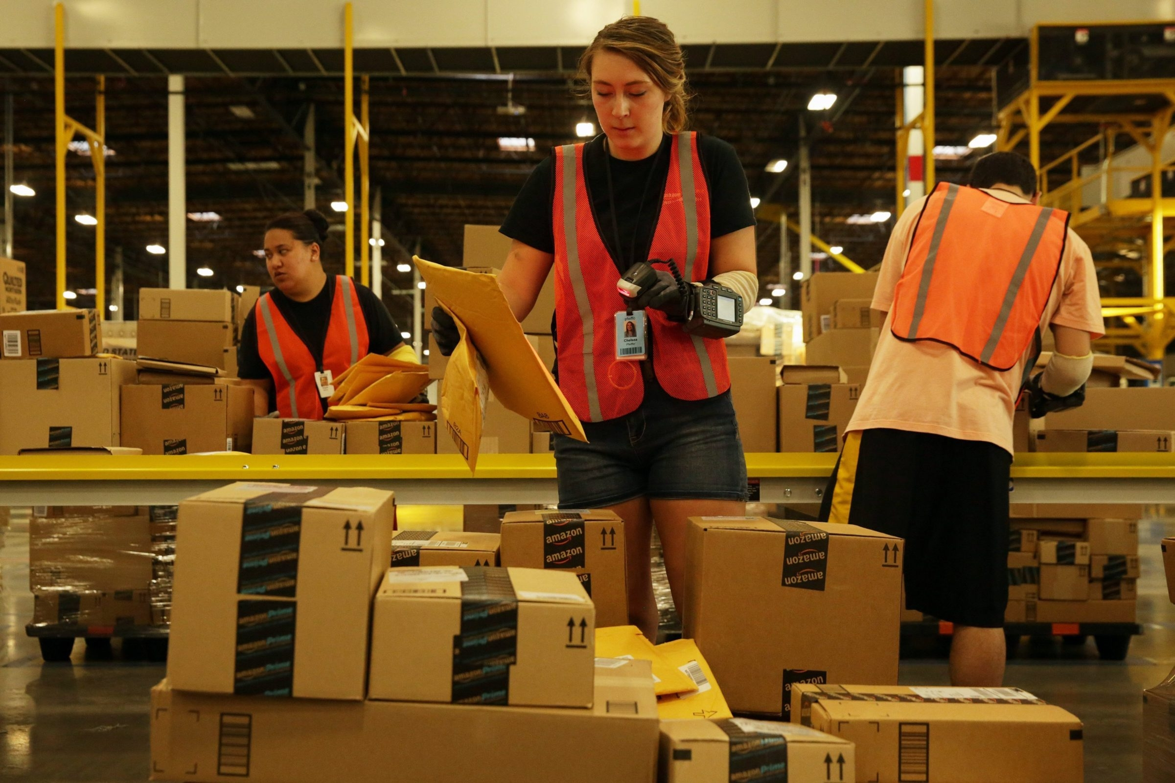 """Chelsea Pfeiffer scans items at Amazon's new sortation center in Kent, Wash. """"Tens of thousands"""" of packages will go through the facility. By the end of the year, Amazon will have more than 15 centers in the U.S."""