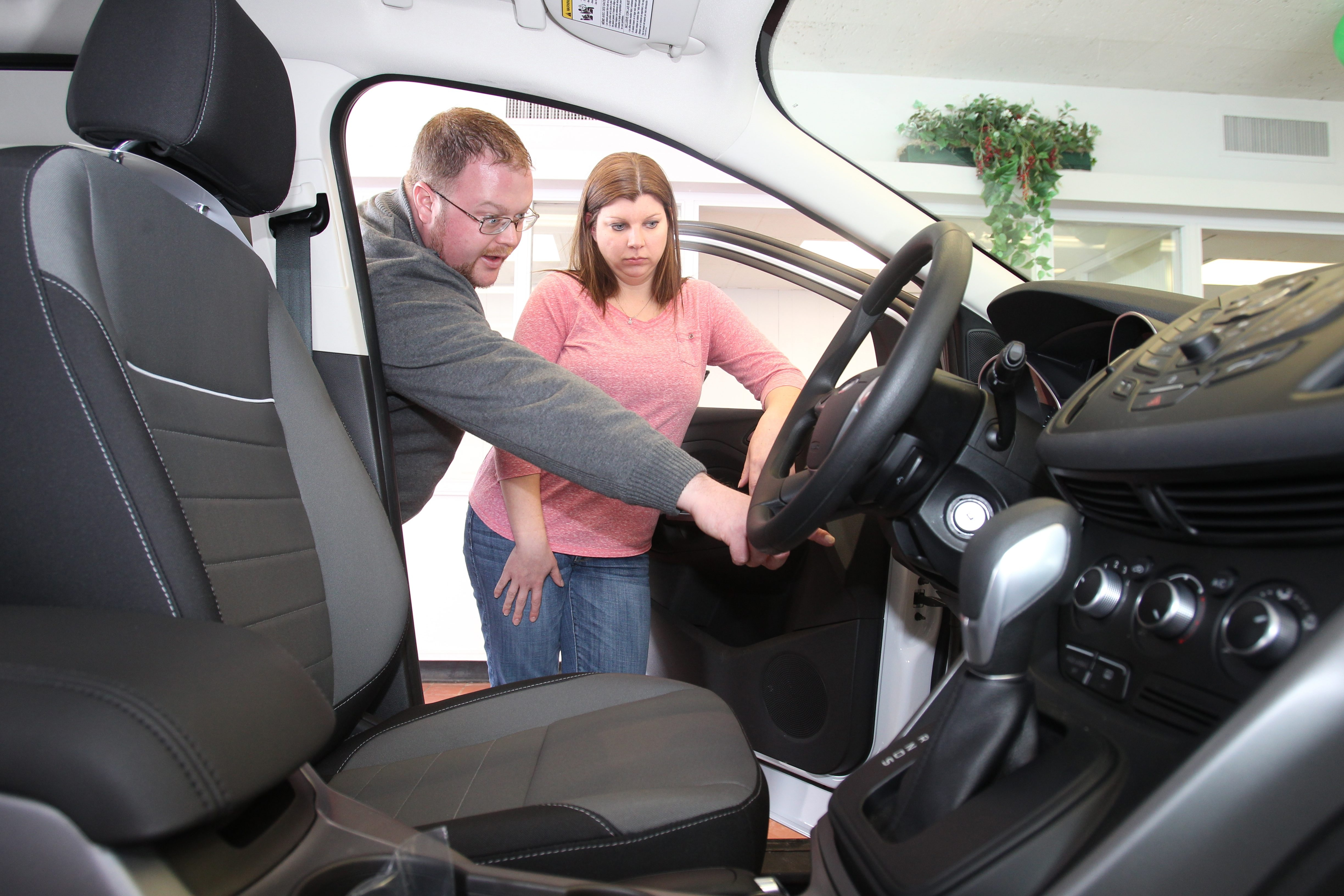 Derek Young, a Ford Certified representative, shows Meghan Sherriff of Lewiston some of the features on a 2014 Ford Escape at Steve Baldo Ford in Niagara Falls.  (John Hickey/Buffalo News)