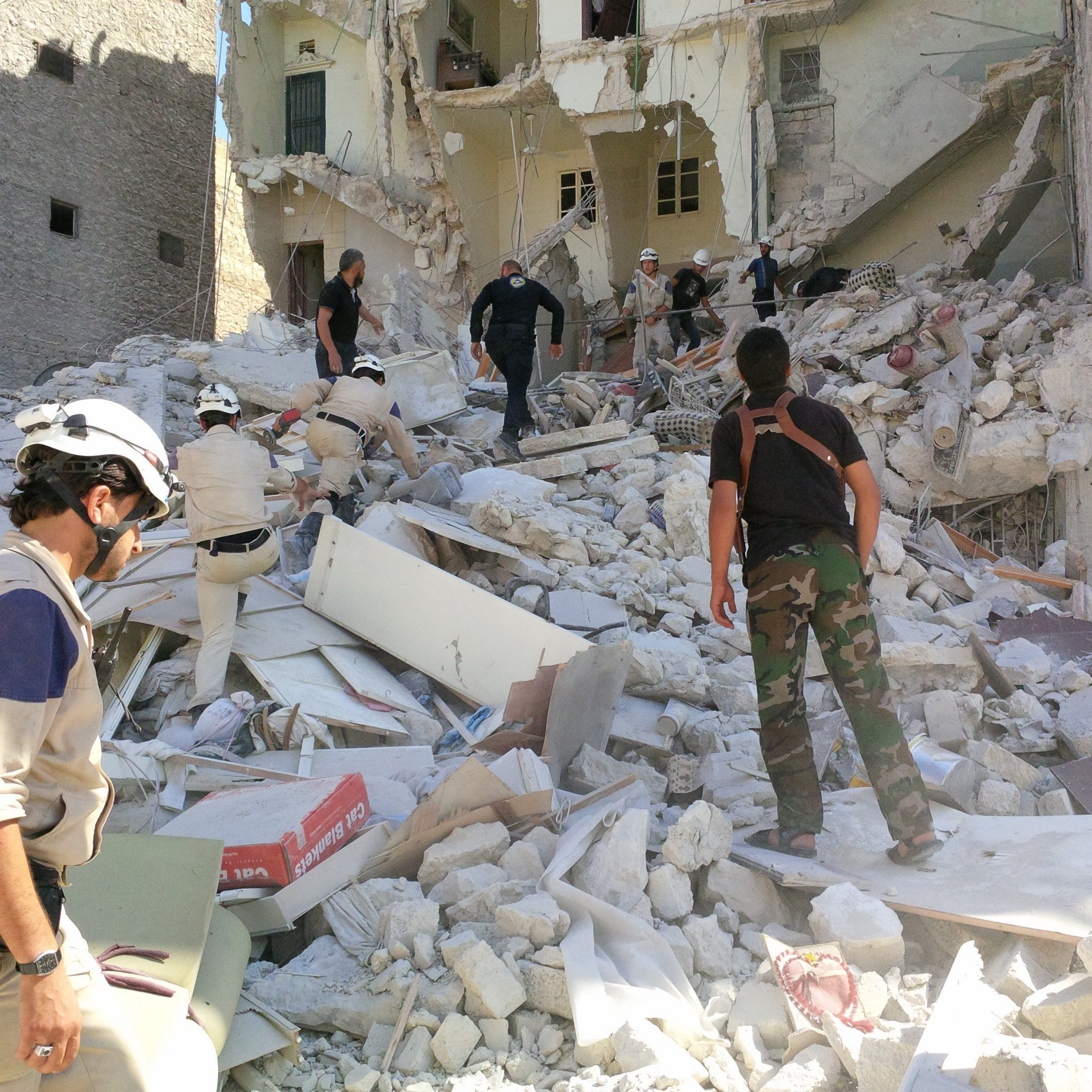Members of Aleppo's civil defense team scramble at the scene of a government barrel bomb attack to rescue a woman trapped in her home, which was sheared in half by the blast.