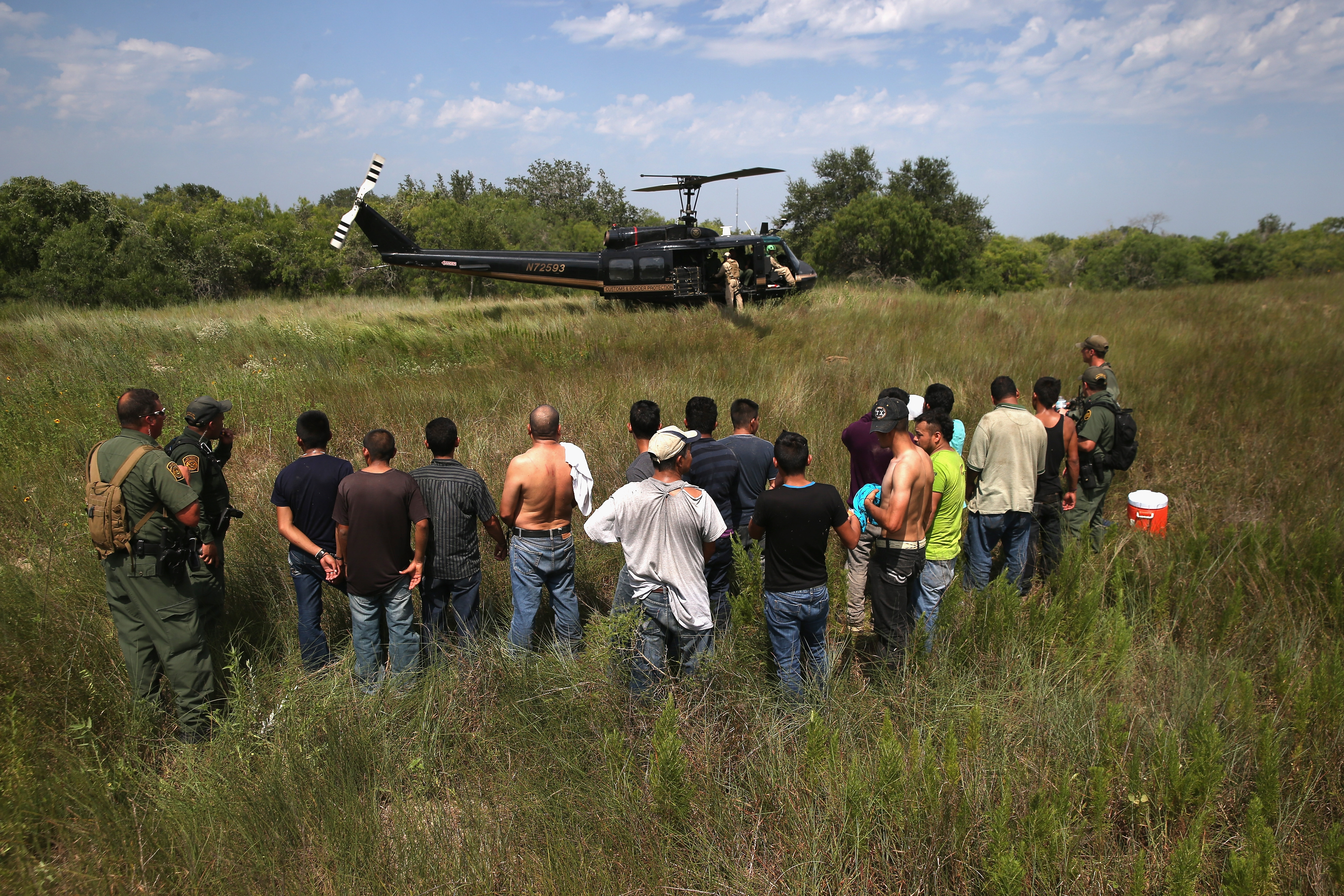 U.S. Border Patrol agents guard undocumented immigrants on July 22 near Falfurrias, Texas, before sending them to a processing center. Texas ranchers have invited armed militias to patrol private land on the U.S.-Mexico border.