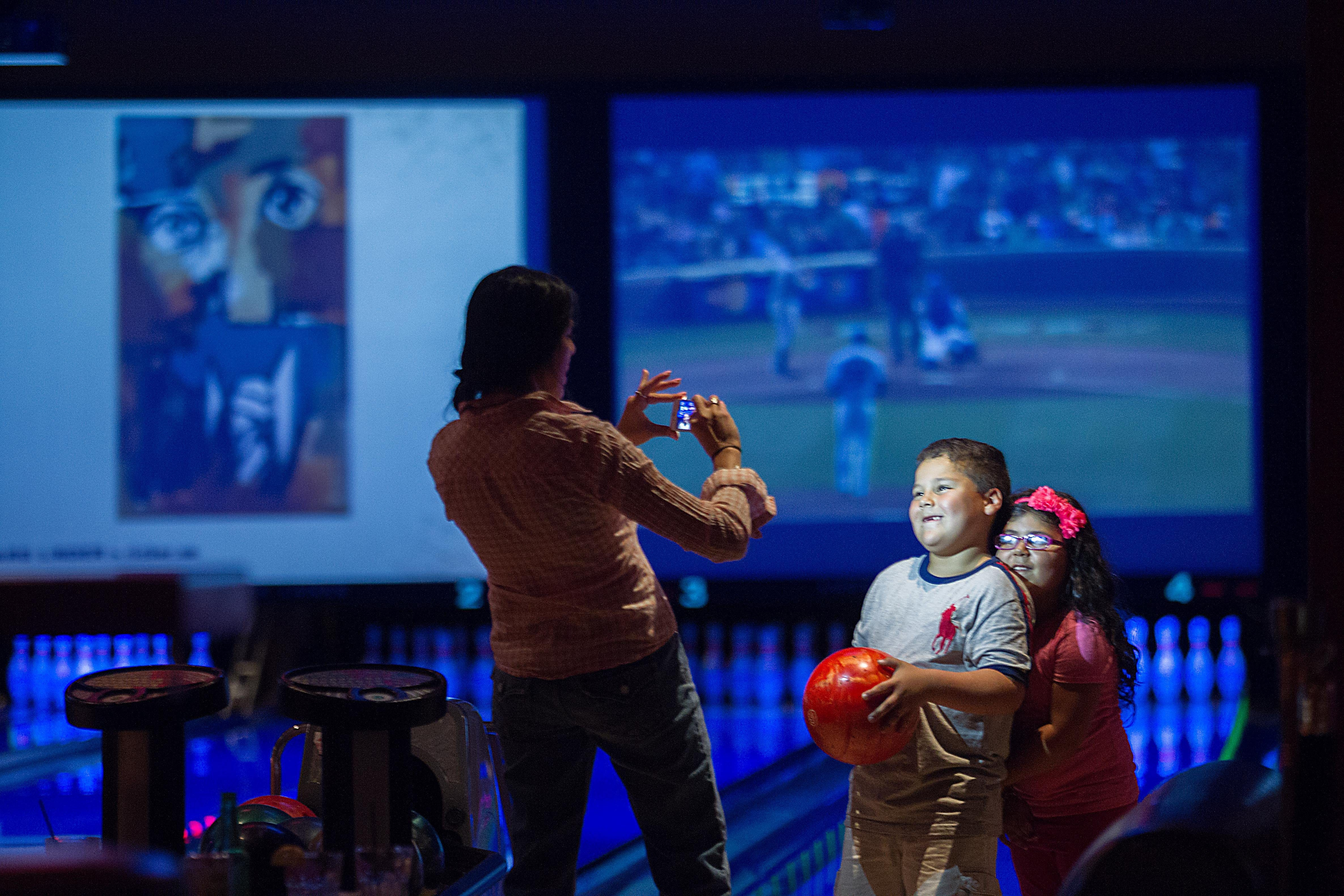 Jacqueline Martinez takes a picture of her son Ryan, 6, and daughter Isabel, 4, as they bowl at Lucky Strike, one of a handful of old-fashioned bowling alleys that still exist in Chicago.