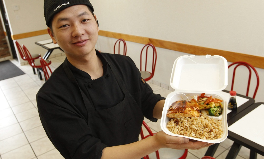 Owner and chef Jim Wang displays a salmon plate with mixed vegetables and fried rice at Winny's Seafood & Steakhouse. (Sharon Cantillon /Buffalo News)