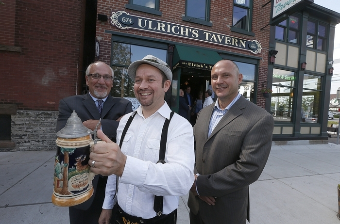 Jim Puskas, center, dressed in German clothing, joins owner Thomas Eoannou, left, and bar proprietor Sal Buscaglia for Ulrich's grand reopening. (Robert Kirkham/Buffalo News)