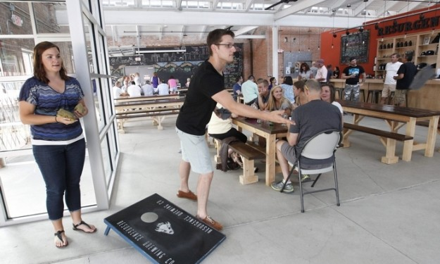 Kelly Yachow, of West Bend, Wis., and Zach Keenan, of Minneapolis, play corn hole at Resurgence Brewing Co. (Sharon Cantillon/Buffalo News)