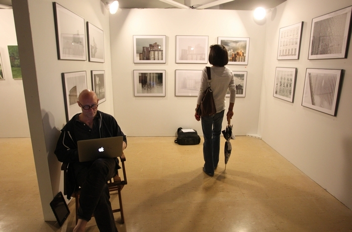 The Echo Art Fair returns to the Central Library this weekend. Here, Thomas Bittner works by his photographs of grain silos at last year's event. (Sharon Cantillon/Buffalo News file photo)