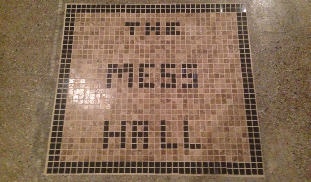 A creative floor block relays the name of the new restaurant, whose opening will be delayed.