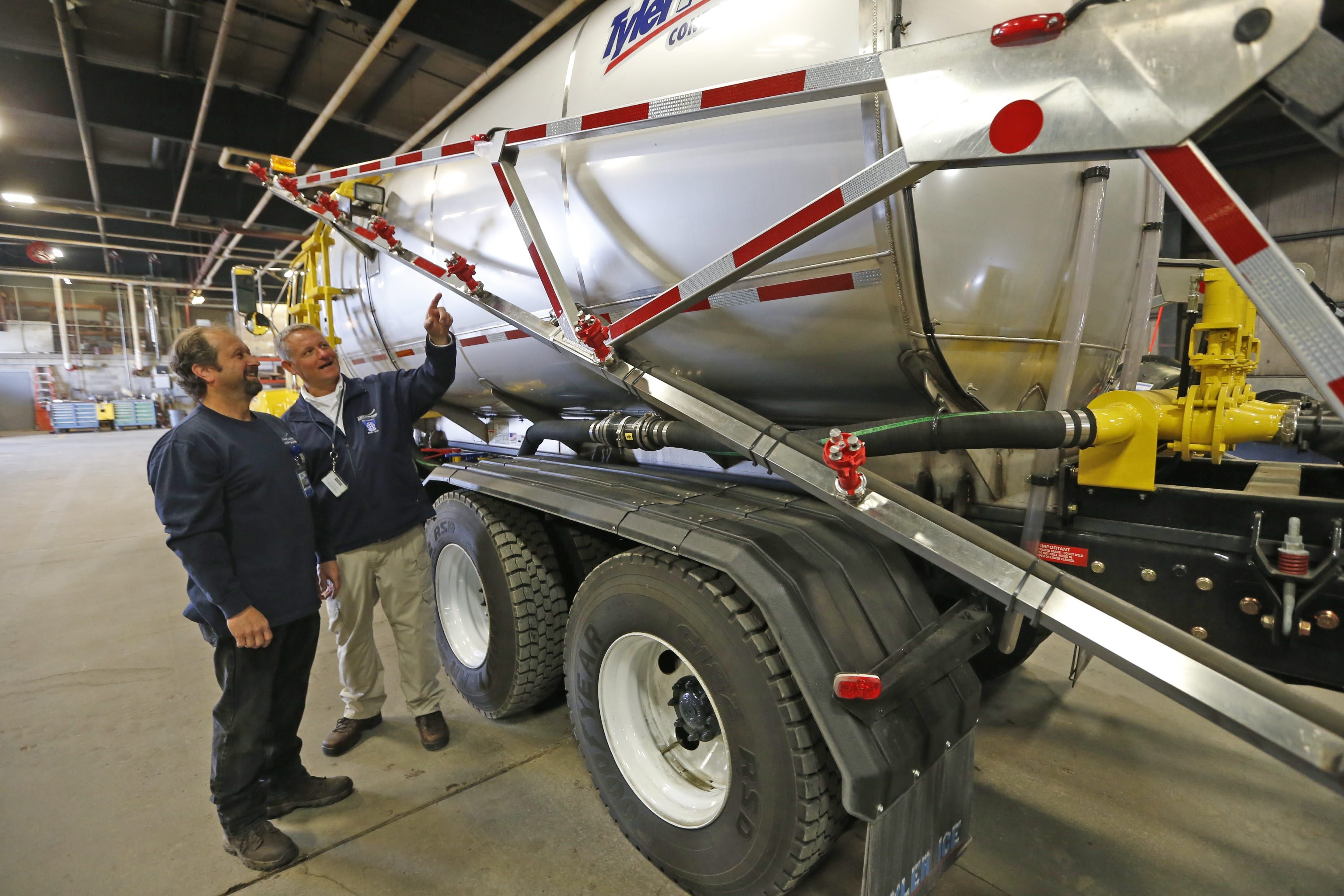 New tanker truck that distributes a liquid that melts snow is gassed up and ready to go as operator John Kwasniewski, left, speaks with airfield supervisor Dennis Eggert.  Snow removal crews at the Buffalo-Niagara International Airport have a new truck and they're prepared for the worst this winter keeping the runways clear.  This was at the airport on Thursday, Oct. 30, 2014.  (Robert Kirkham/Buffalo News)