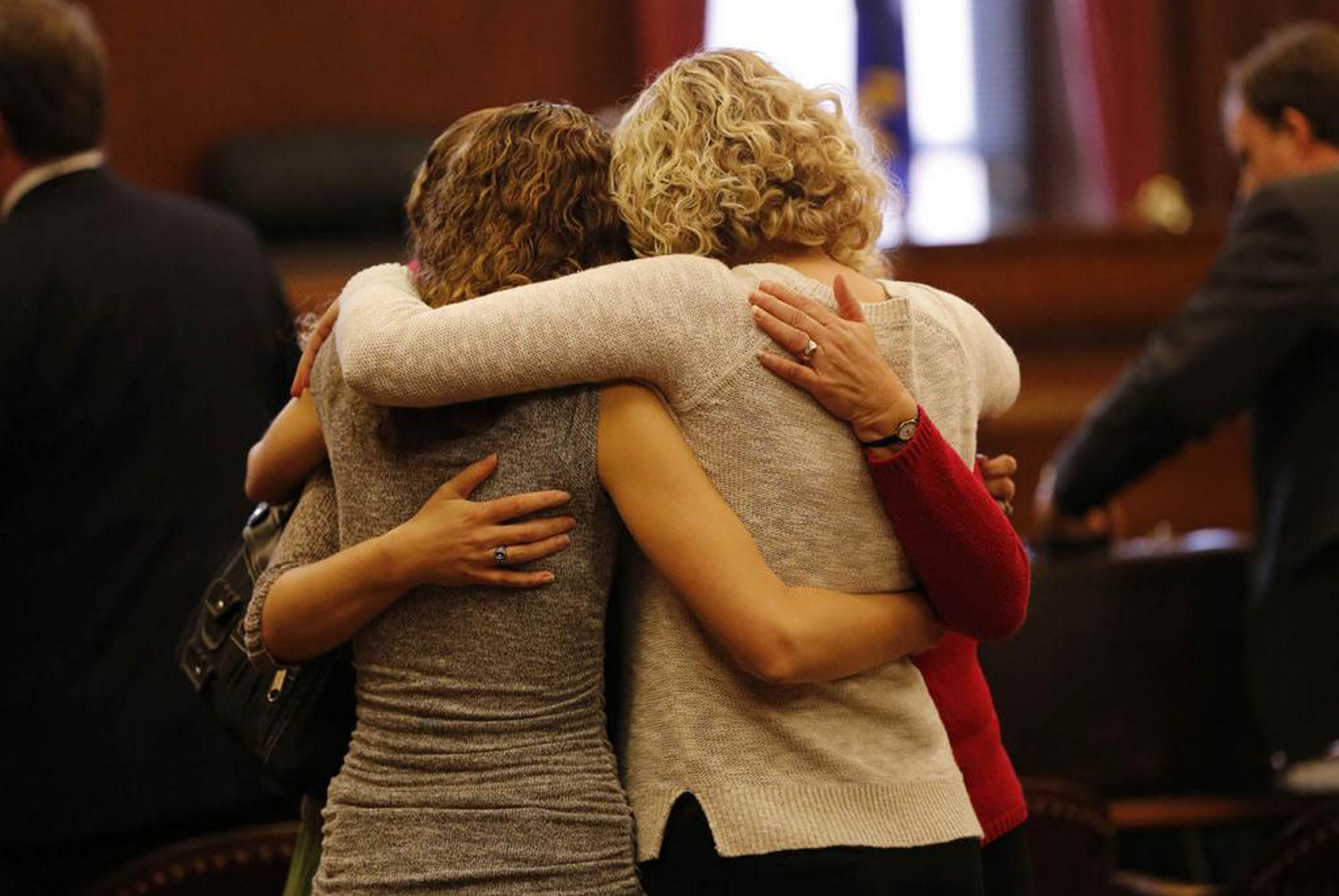 Karen Wielinski and her daughters embrace in the courtroom today after a confidential settlement was reached in their lawsuit over the death of Wielinski's husband when Flight 3407 crashed into their Clarence Center home. (Derek Gee/Buffalo News)