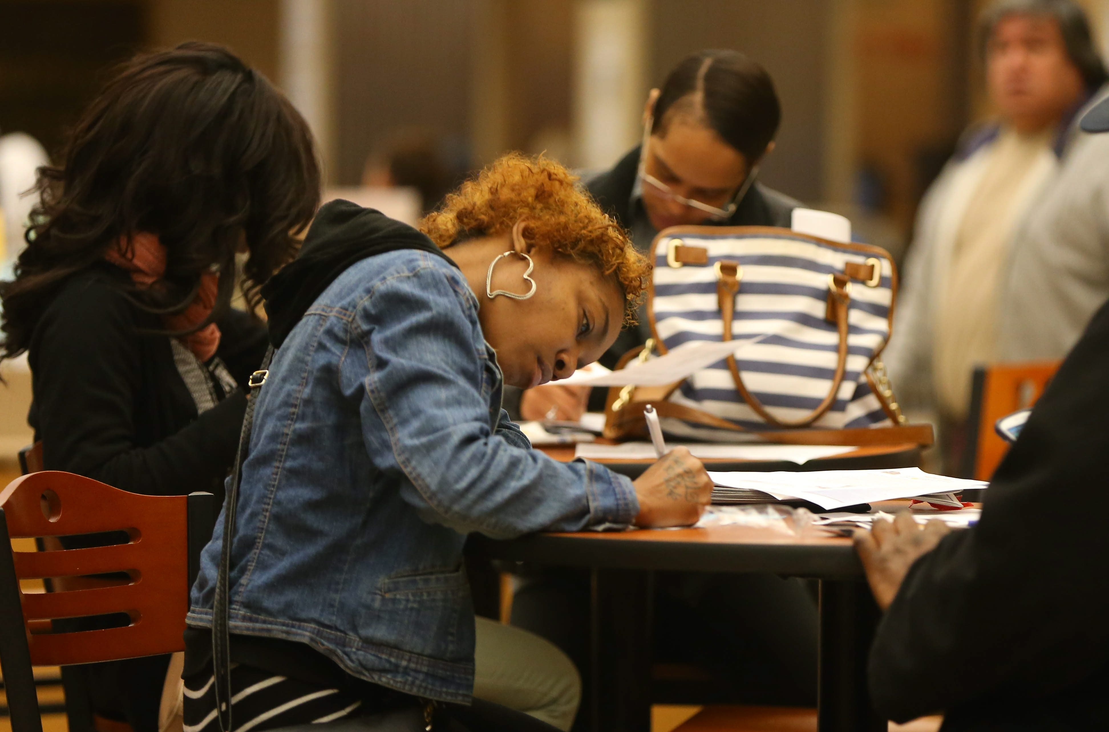 Monique Walton of Buffalo fills out an application at Autumn Diversity Career Fair in the Central Library.